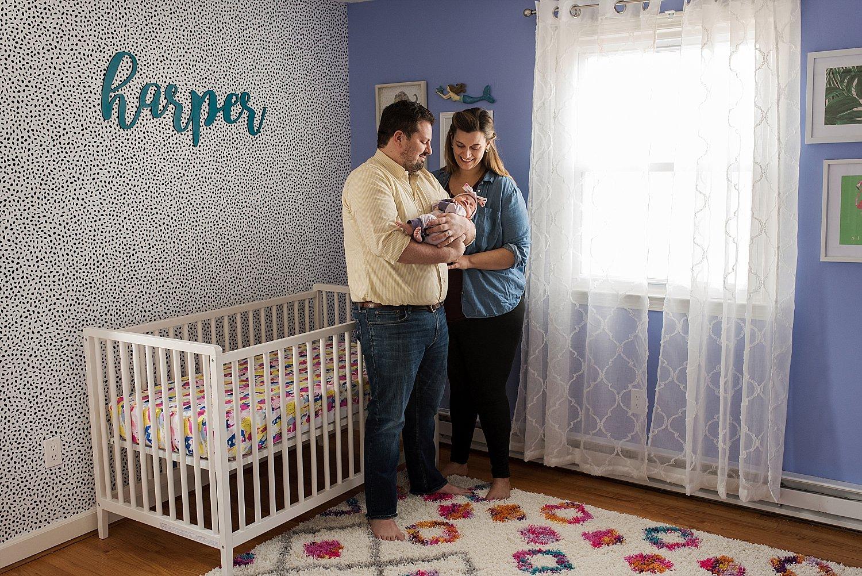 Newborn photography ct. Mom and dad holding newborn baby in nursery