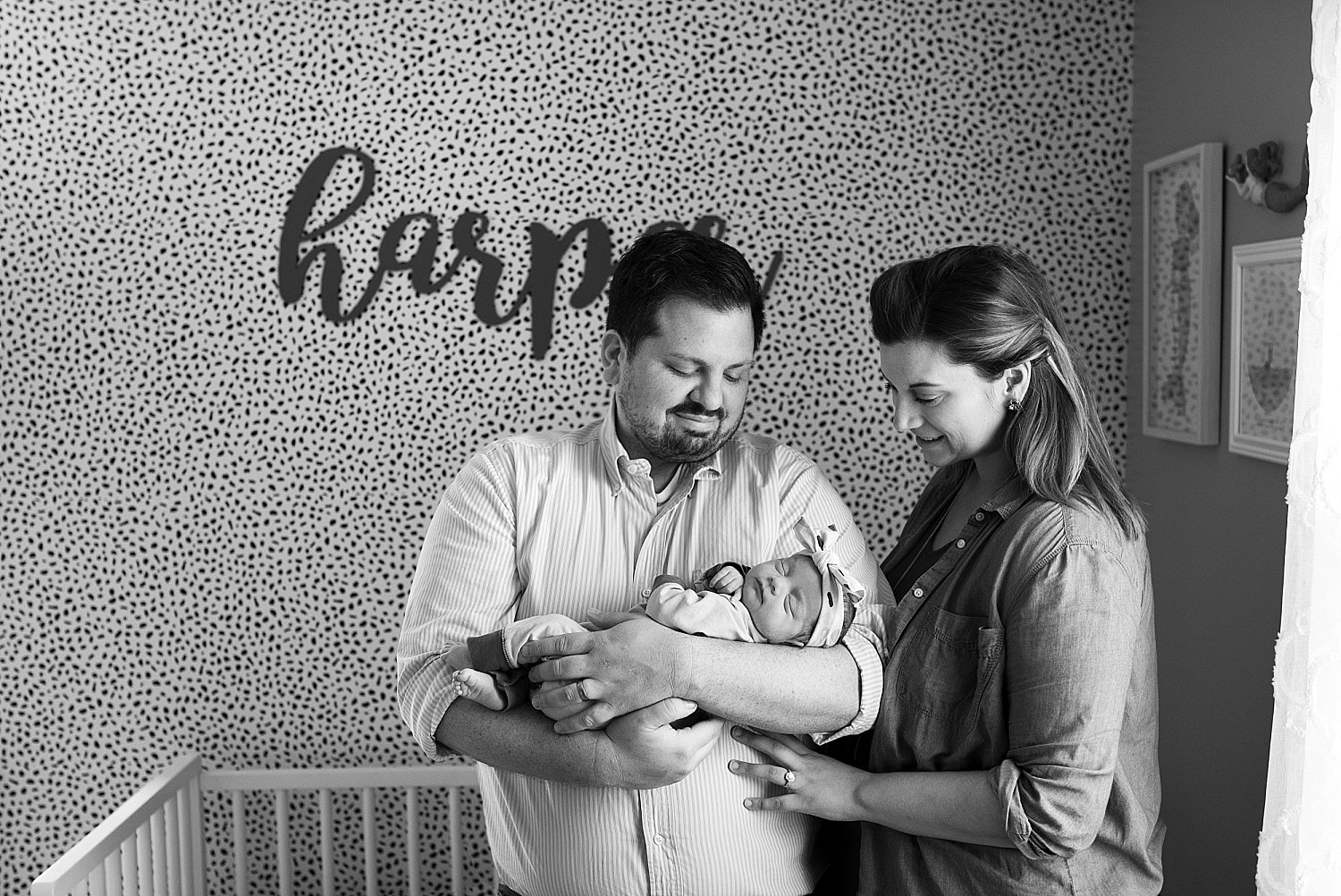New parents holding their baby daughter in her nursery during connecticut newborn photography