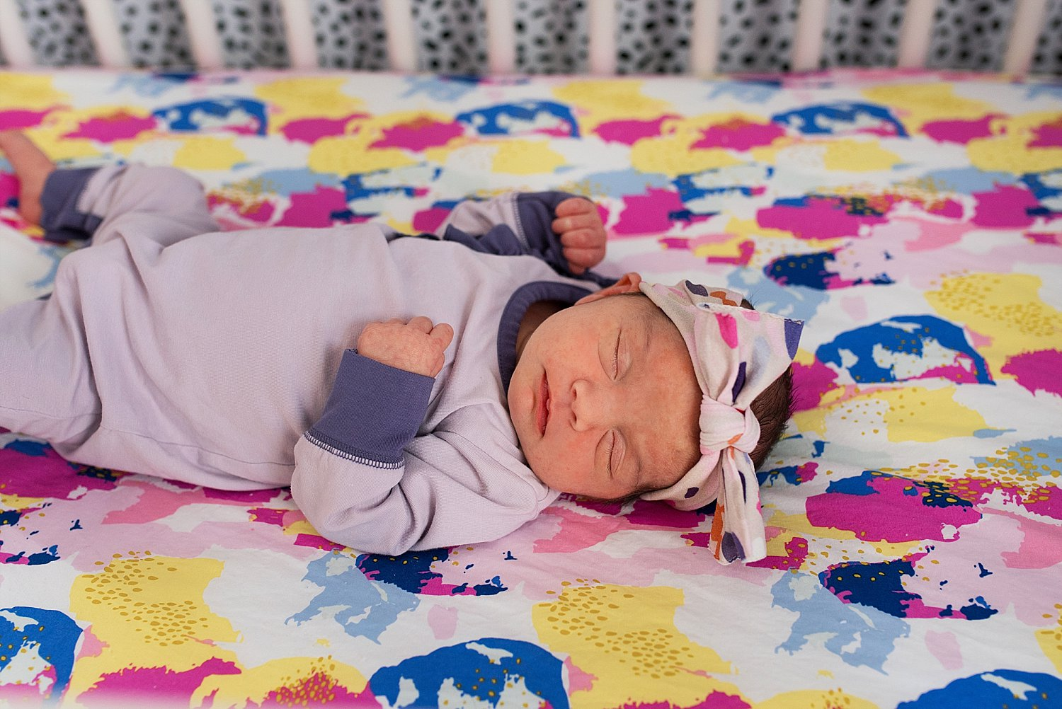 Baby girl laying in her crib with her colorful crib sheets. Newborn photography CT