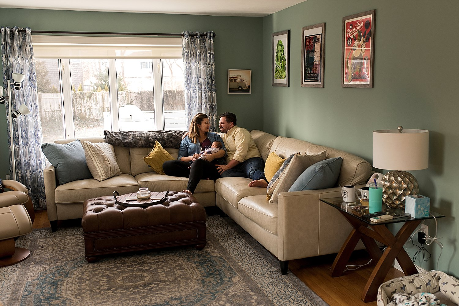 Mom and Dad posing on couch during connecticut newborn photo session
