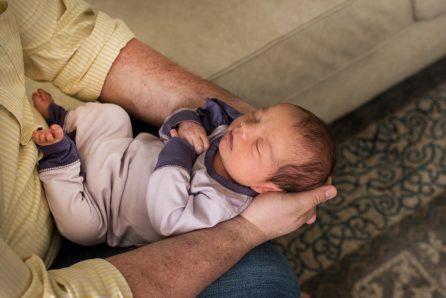 Baby laying in Dad's arms while wearing a purple outfit during her CT newborn photography session
