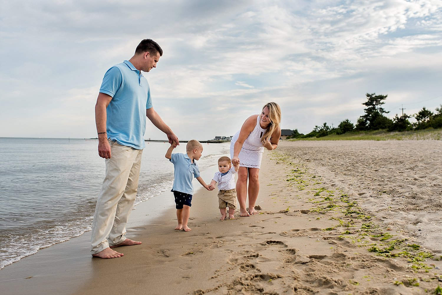 CT family photographer. Family holding hands at the beach during Connecticut family photography