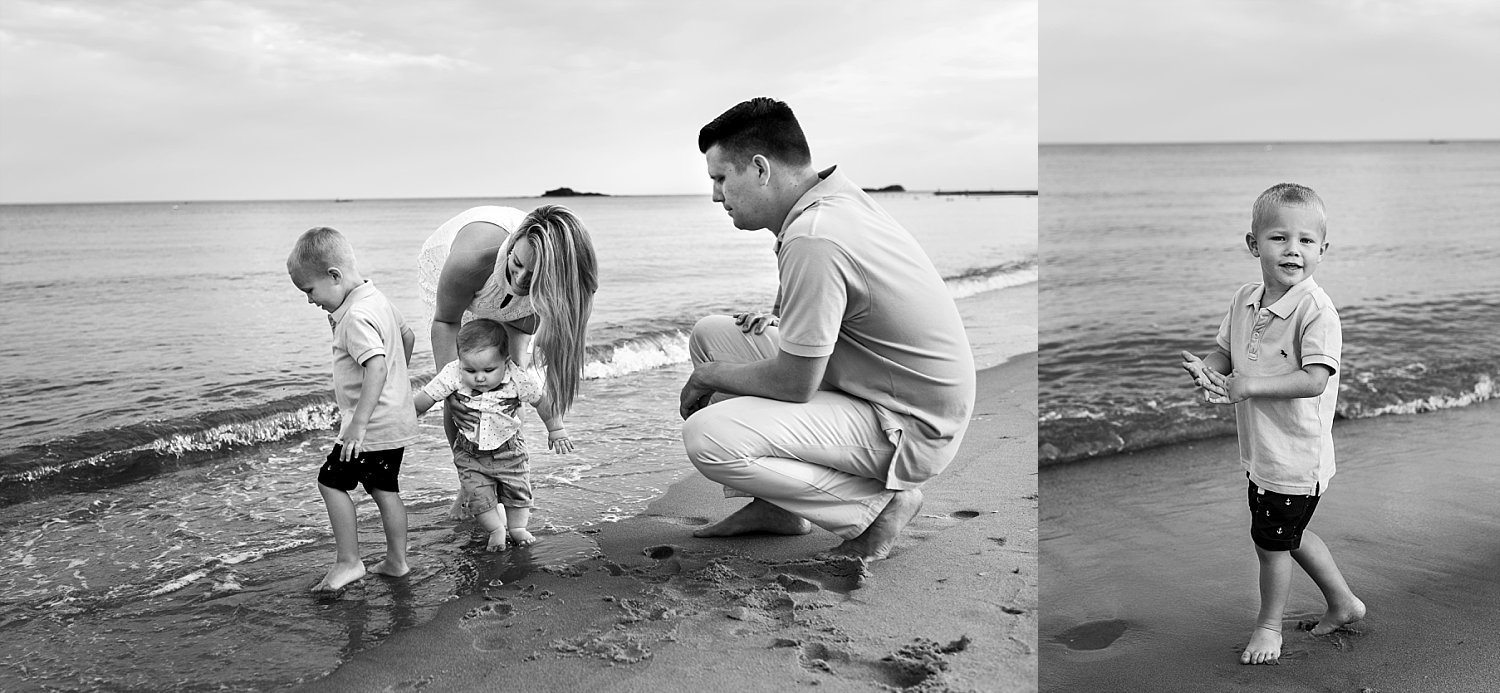 Connecticut family photographer. Mom and Dad playing in the ocean with children during Westbrook, CT photography