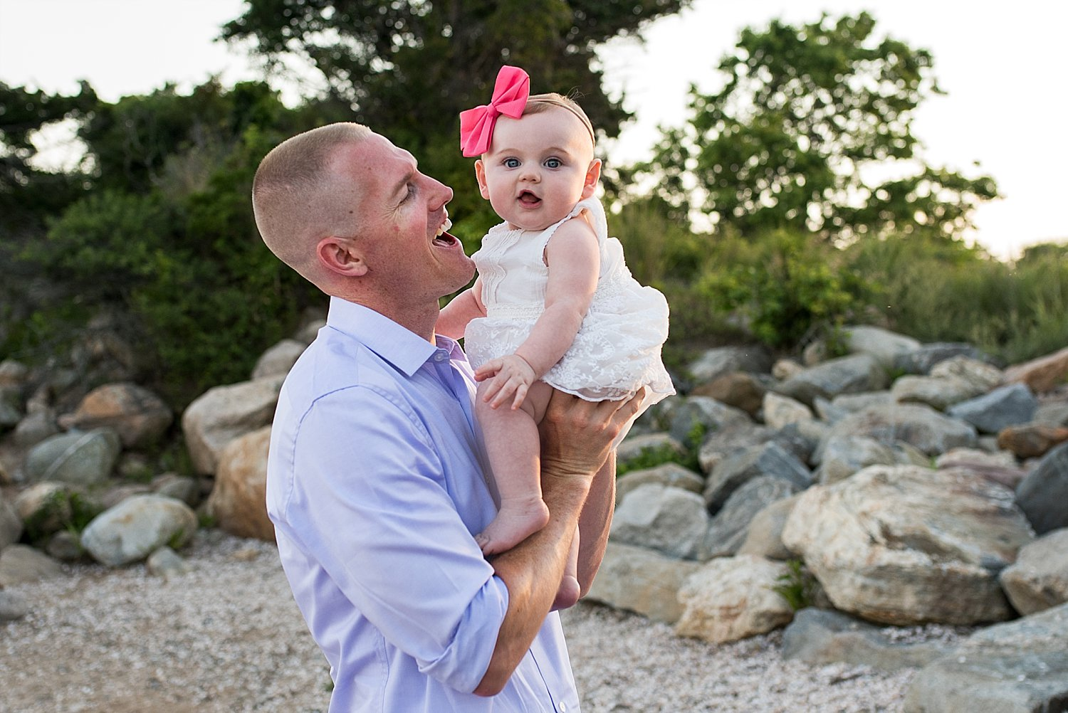 Dad holding baby girl in pink bow during Connecticut family photography