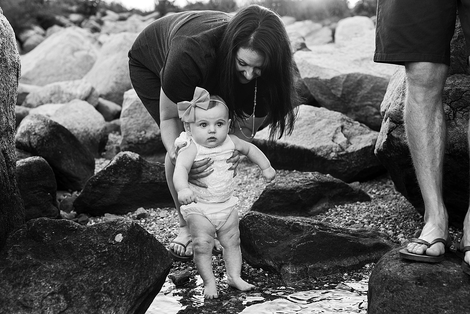 Baby girl tipping her feet in the ocean for the first time at her CT family photo session