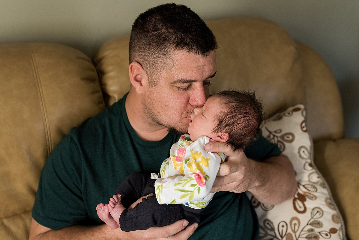 Father kissing newborn baby during CT baby photography.