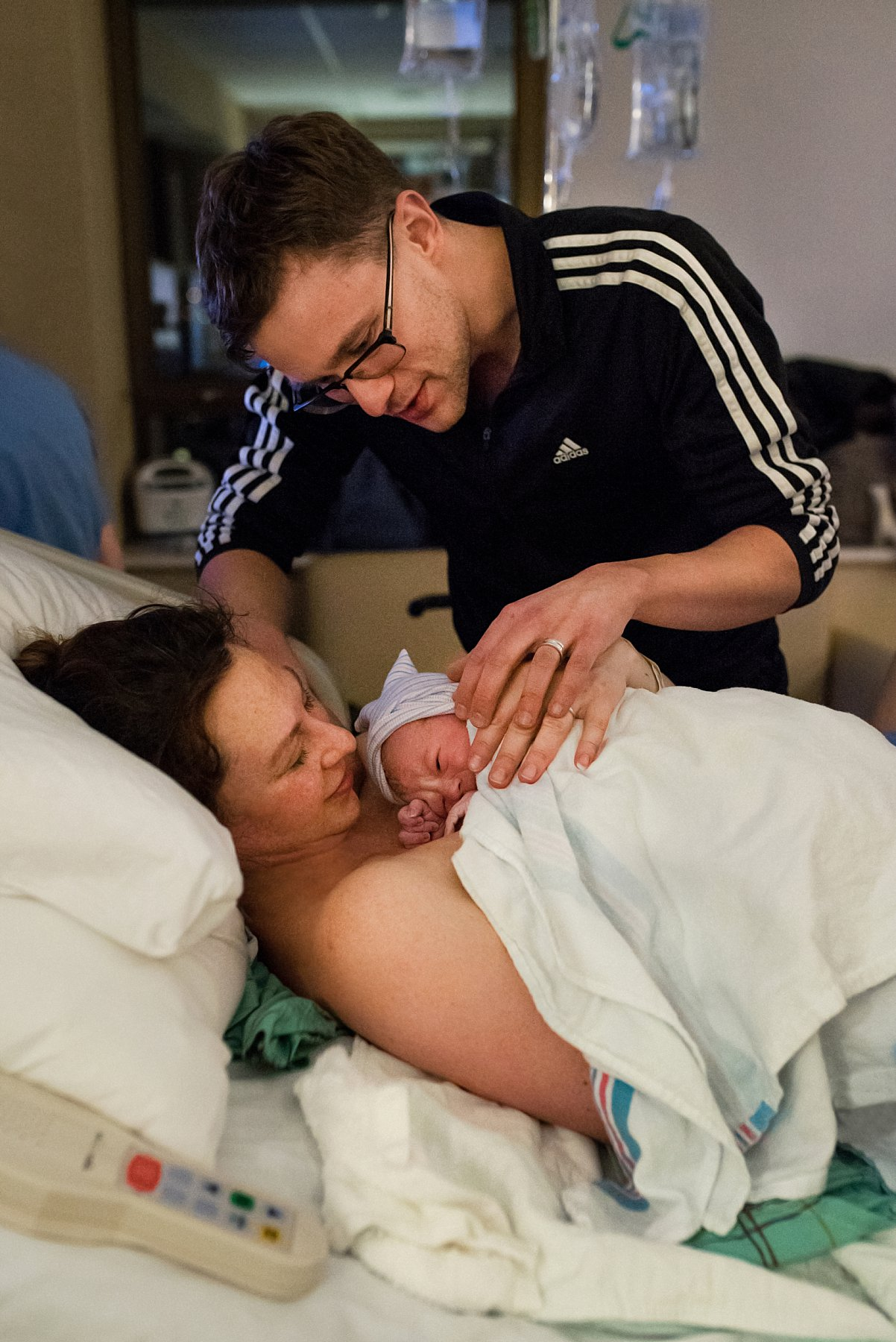 Birth photographer Connecticut. Father meeting newborn daughter for the first time after delivery.