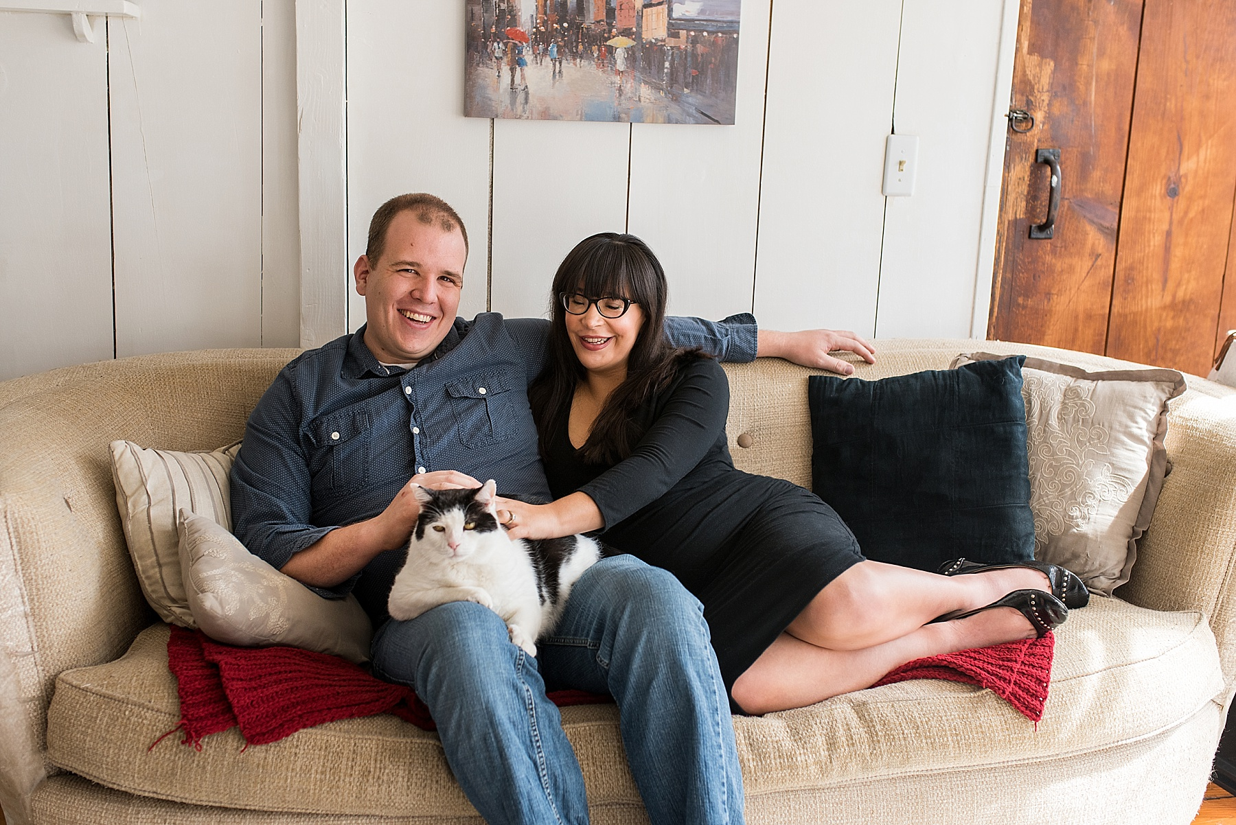 Husband and wife sitting on the couch with their cat during CT maternity photography