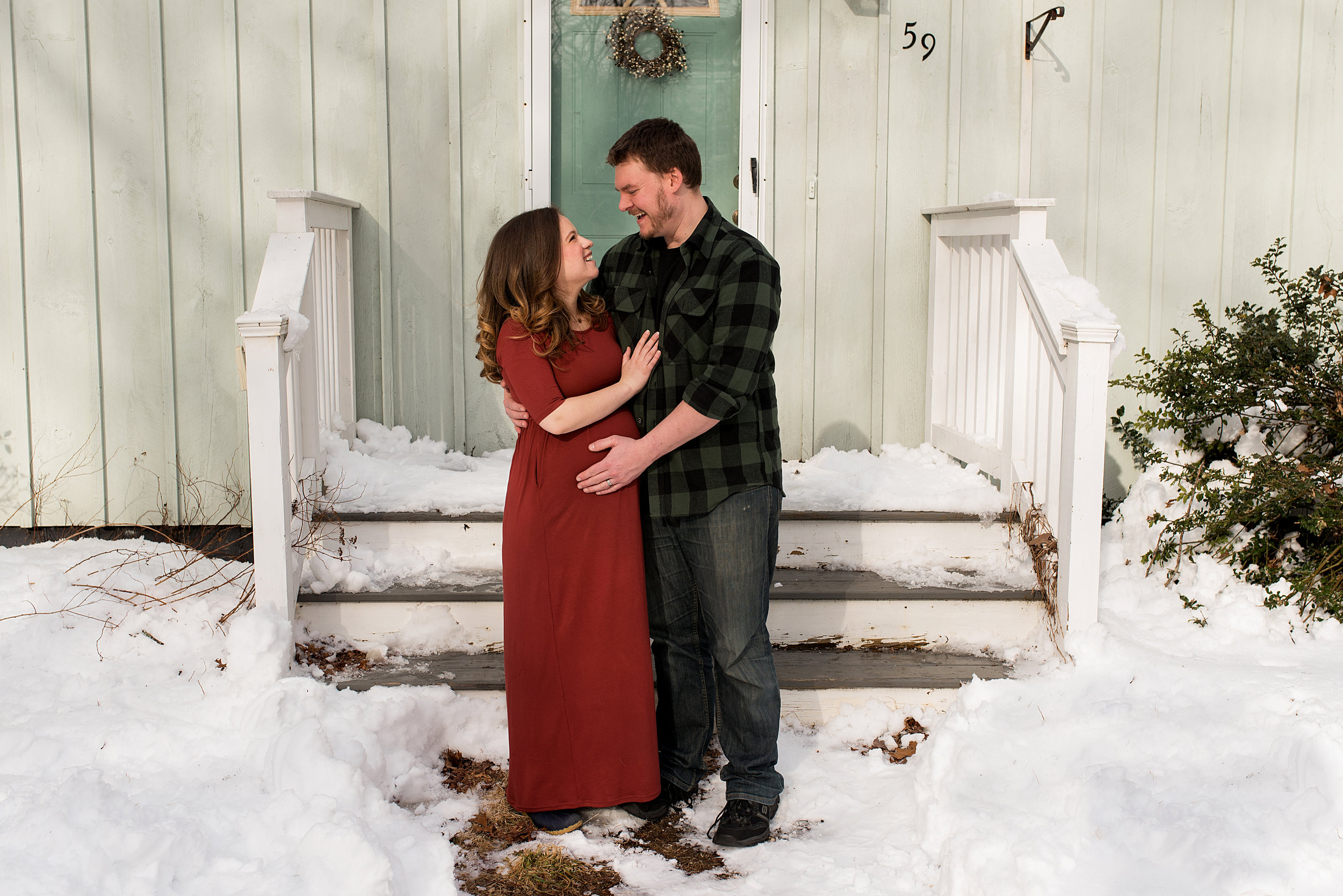 CT maternity photography. husband and wife standing in the snow during maternity portraits.