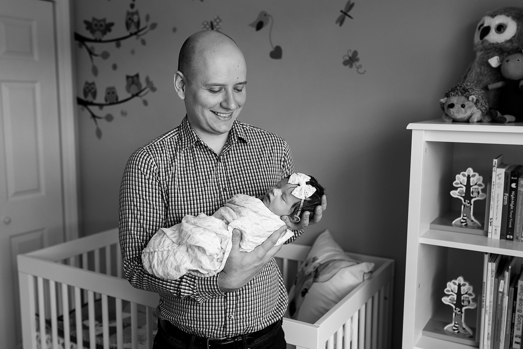 dad smiling while holding newborn daughter during CT baby photography