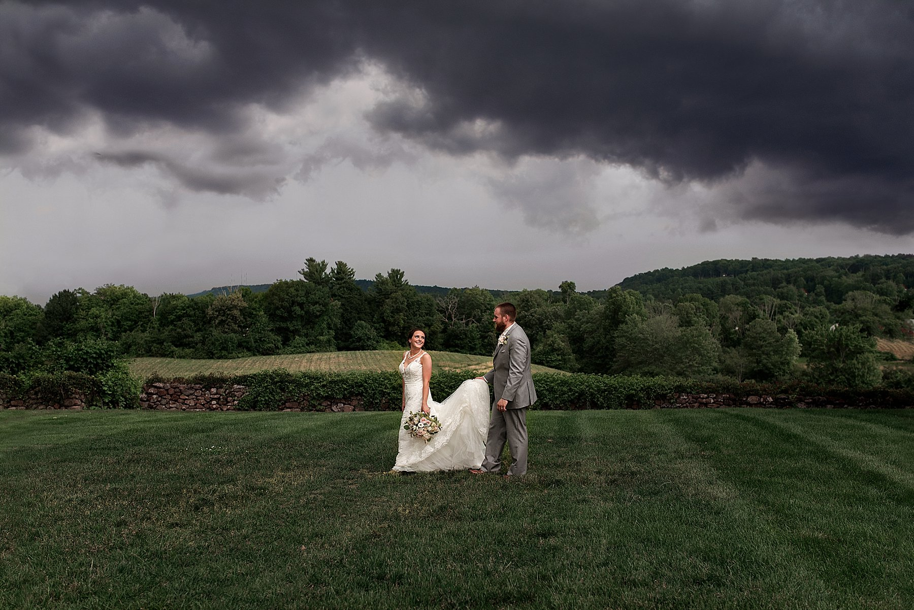 groom holding brides dress during storm on wedding day in CT