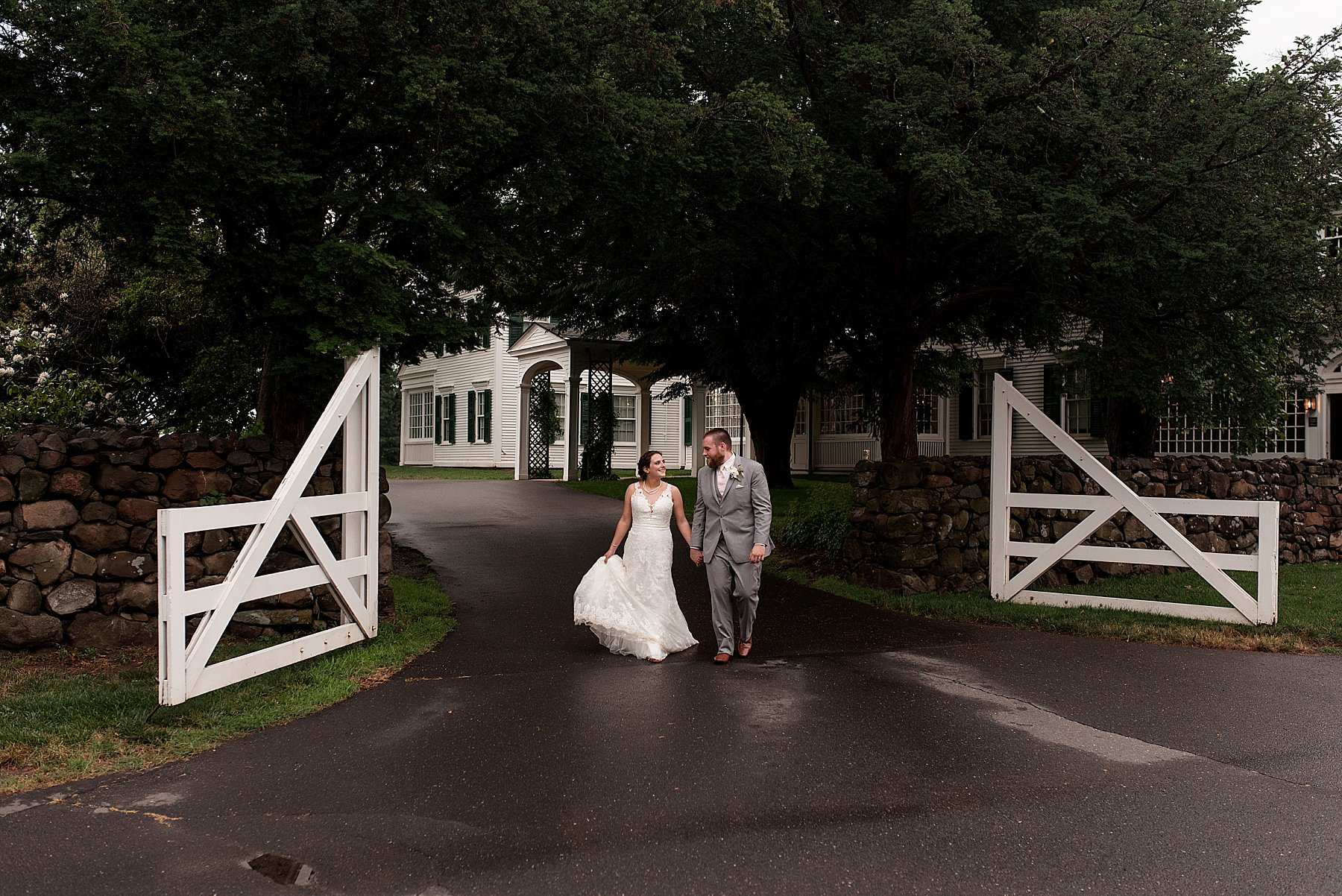 bride and groom walking in the rain on their wedding day in Connecticut