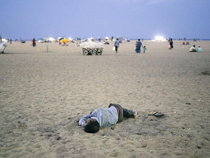 A man sleeping on the beach.