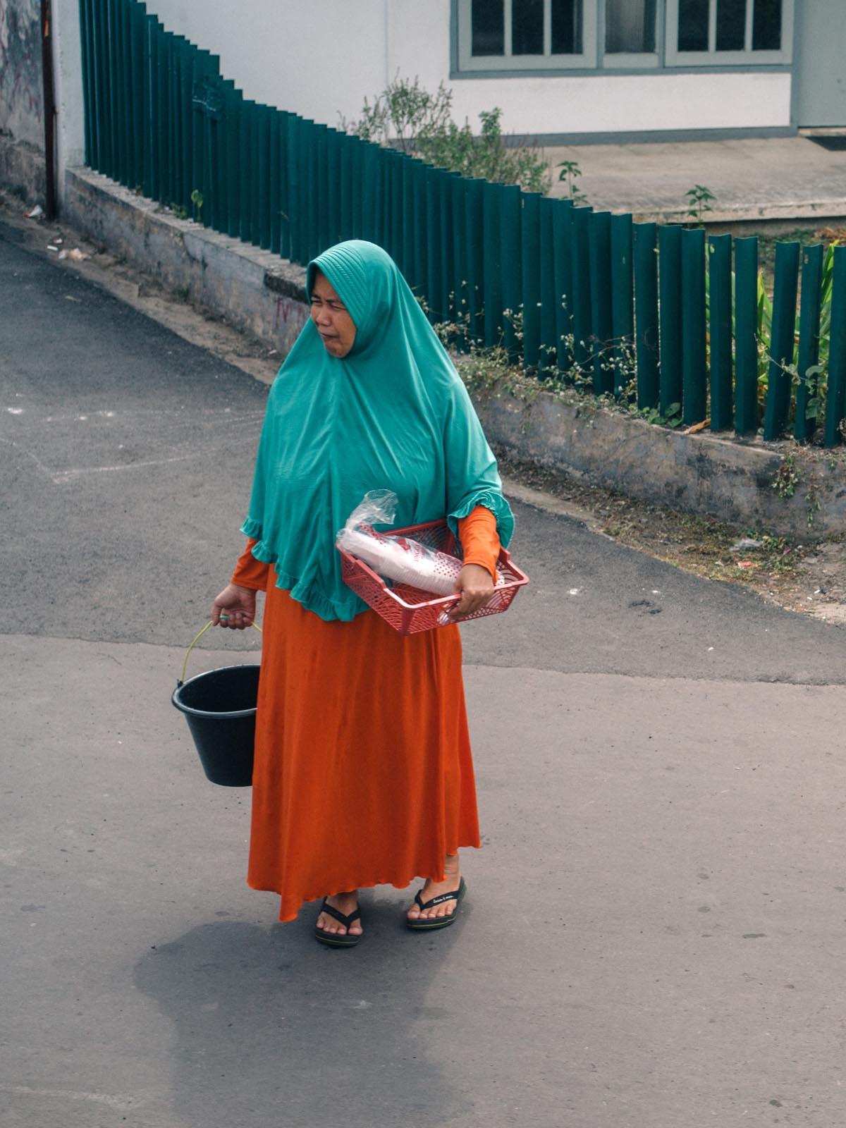 Woman waiting to cross the tracks.