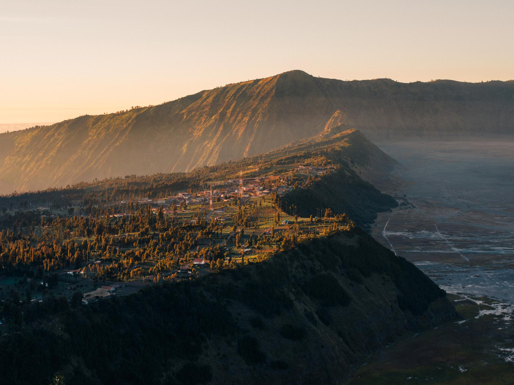 View of the town of Cemoro Lawang at sunrise. On the right: the Sea of Sand and the main caldera.