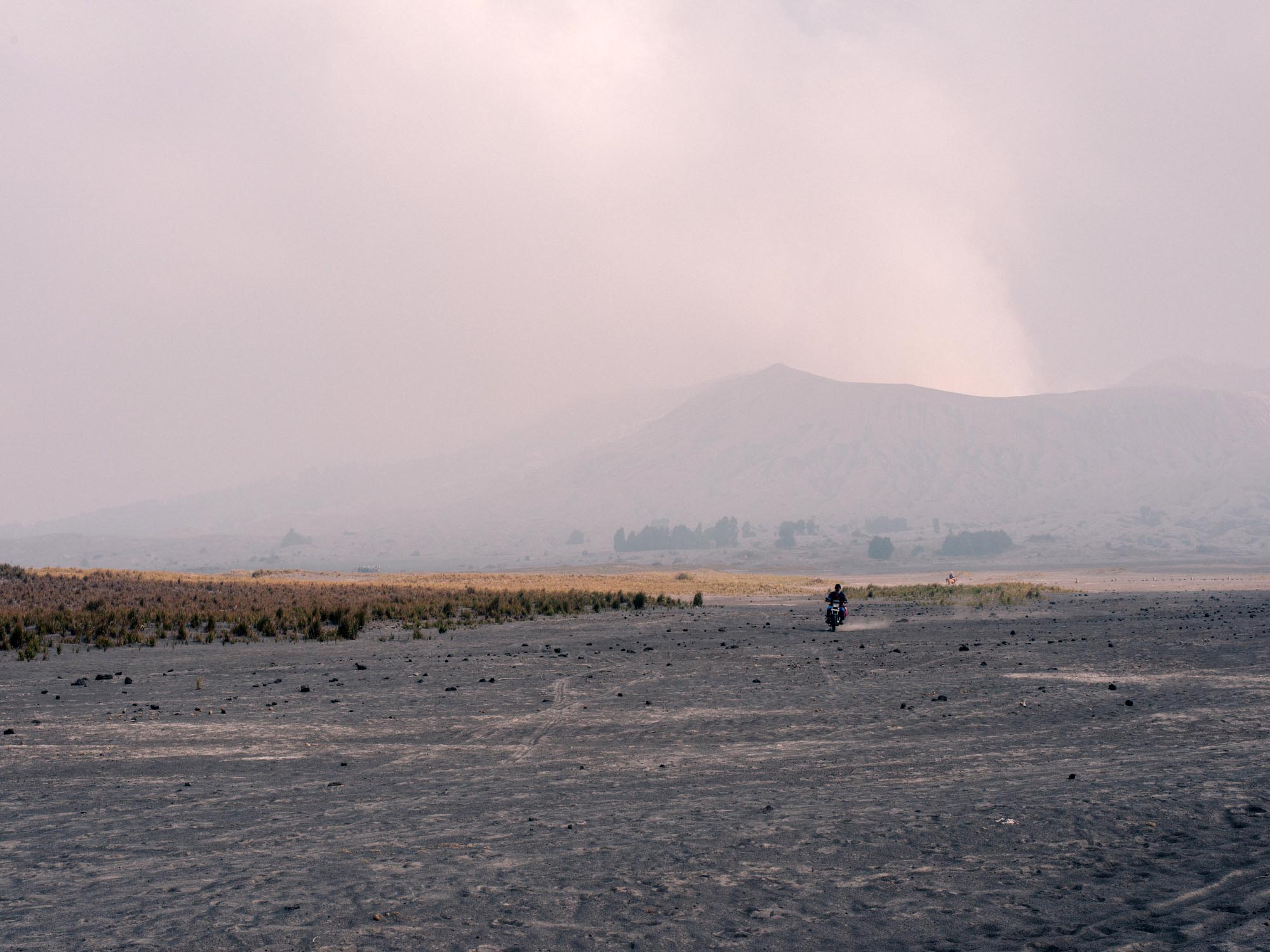 A lonely local crossing the Sea of Sand. Smoking Bromo in the back.