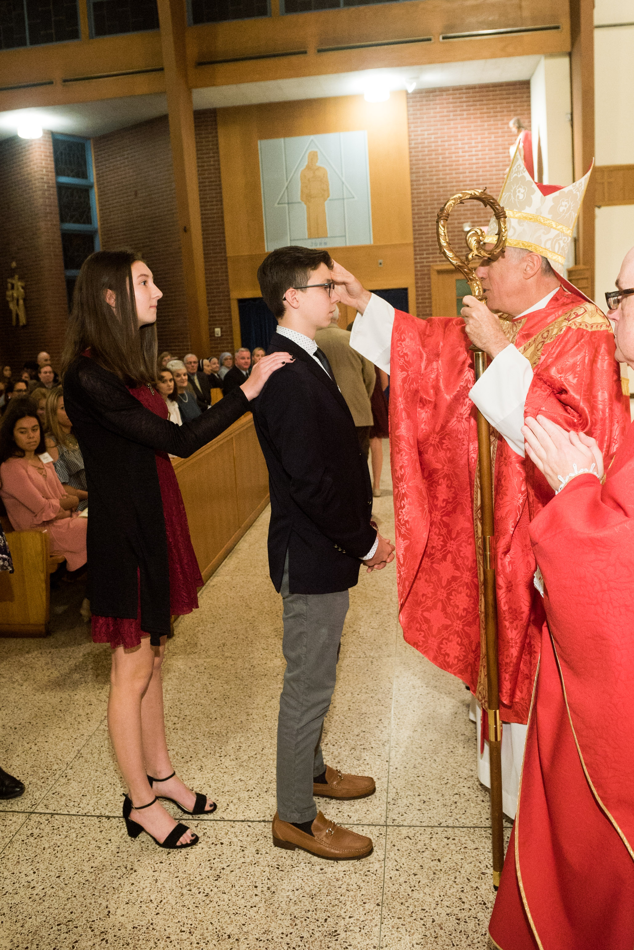 Bishop Checchio anointing Spencer THOMAS MORE Wood with the Sacred Chrism Oil at Sunday's Confirmation Mass.