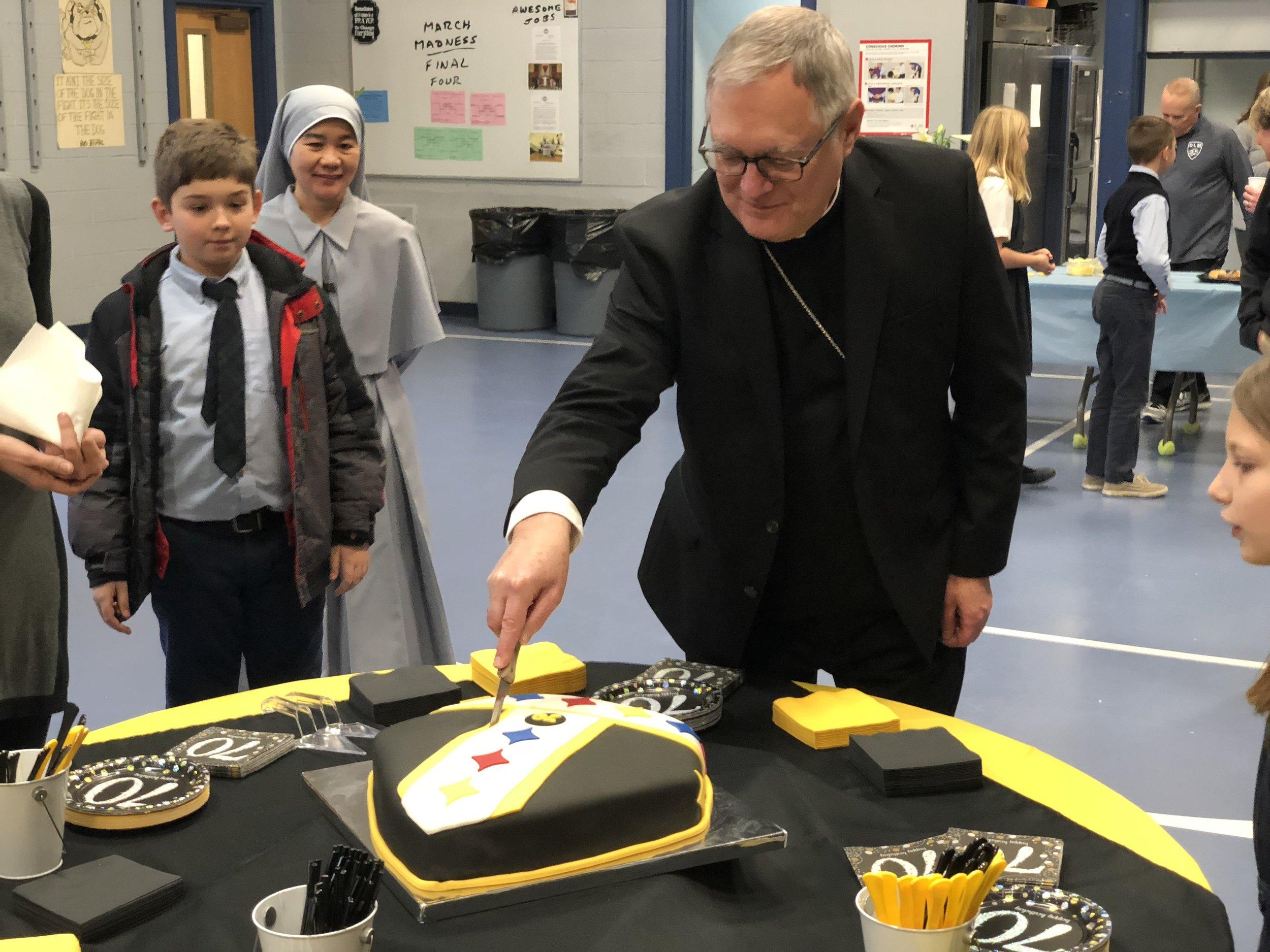 Bishop Tobin happily cuts his birthday cake!