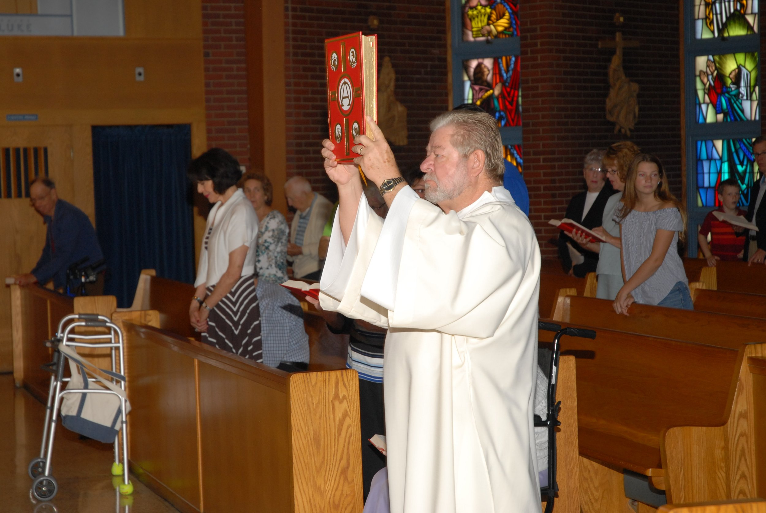 Deacon John Dowd carries the Book of the Gospel.
