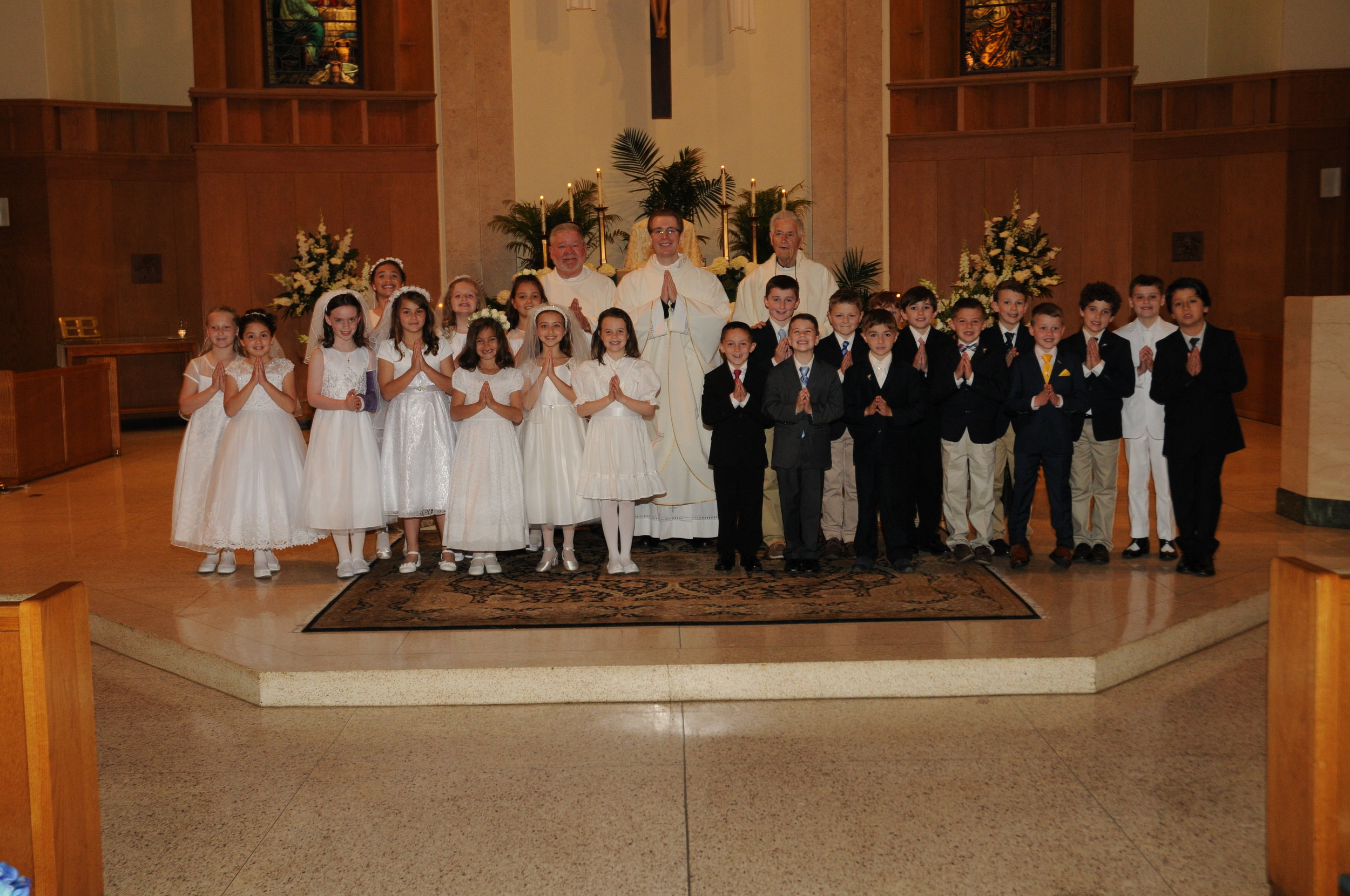 The Our Lady of Mercy School First Communion Class with Fr. Barrow, Associate Pastor of OLM, Fr. John Gray, Senior Priest of Providence and Deacon John Dowd, OLM Deacon on May 12, 2018.