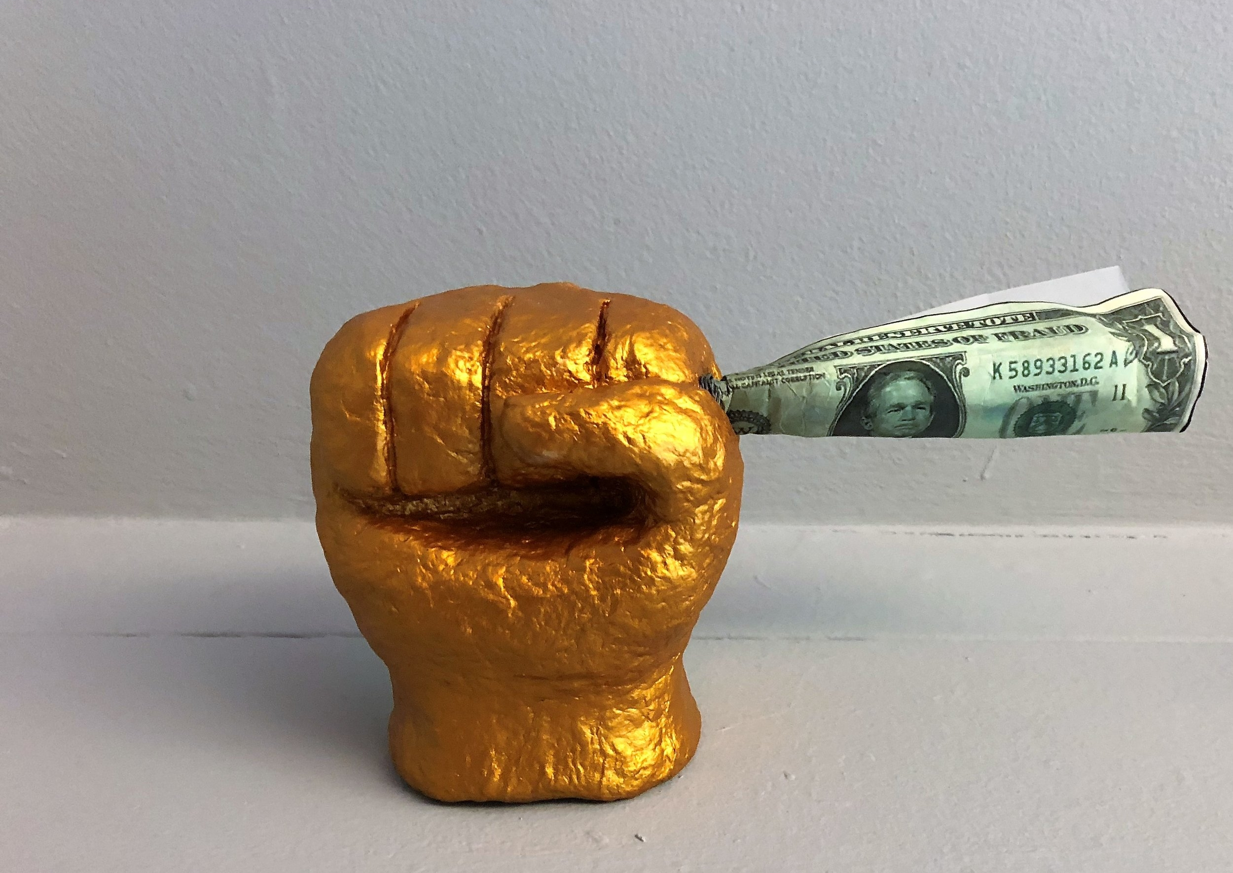 Fist Holding Money   This piece came to me while looking at George W. Bush face on the Dollar Bill. The thought of him and Dick Chaney investing in private prisons captures the capitalization of justice. The golden power fist holds the money to be made in prisons.  I have been locked in solitary confinement for over 25 years with limited access to the outside world. Despite my obvious indigency, I am tapped financially for music, calls, food, and more. I even pay a medical co-pay to McKesson Pharmaceuticals, the company that will also provide the drug to execute me.    Sold