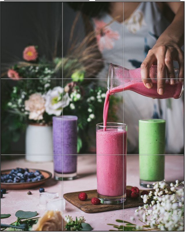 In this photo, the main element is the pink smoothie in the front and the pouring action. One of the intersection points hits the pink smoothie, another point hits the pouring vessel, and a third point hits the purple smoothie in the back.
