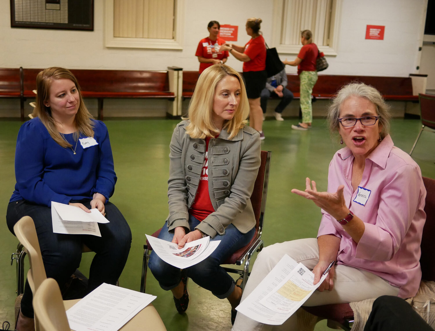 Katy Bloomberg, left, Maureen McGee, center, and Veronica Bartlett, right, train to canvass voters with the group Moms Demand Action in Arlington.Daniella     Cheslow / WAMU