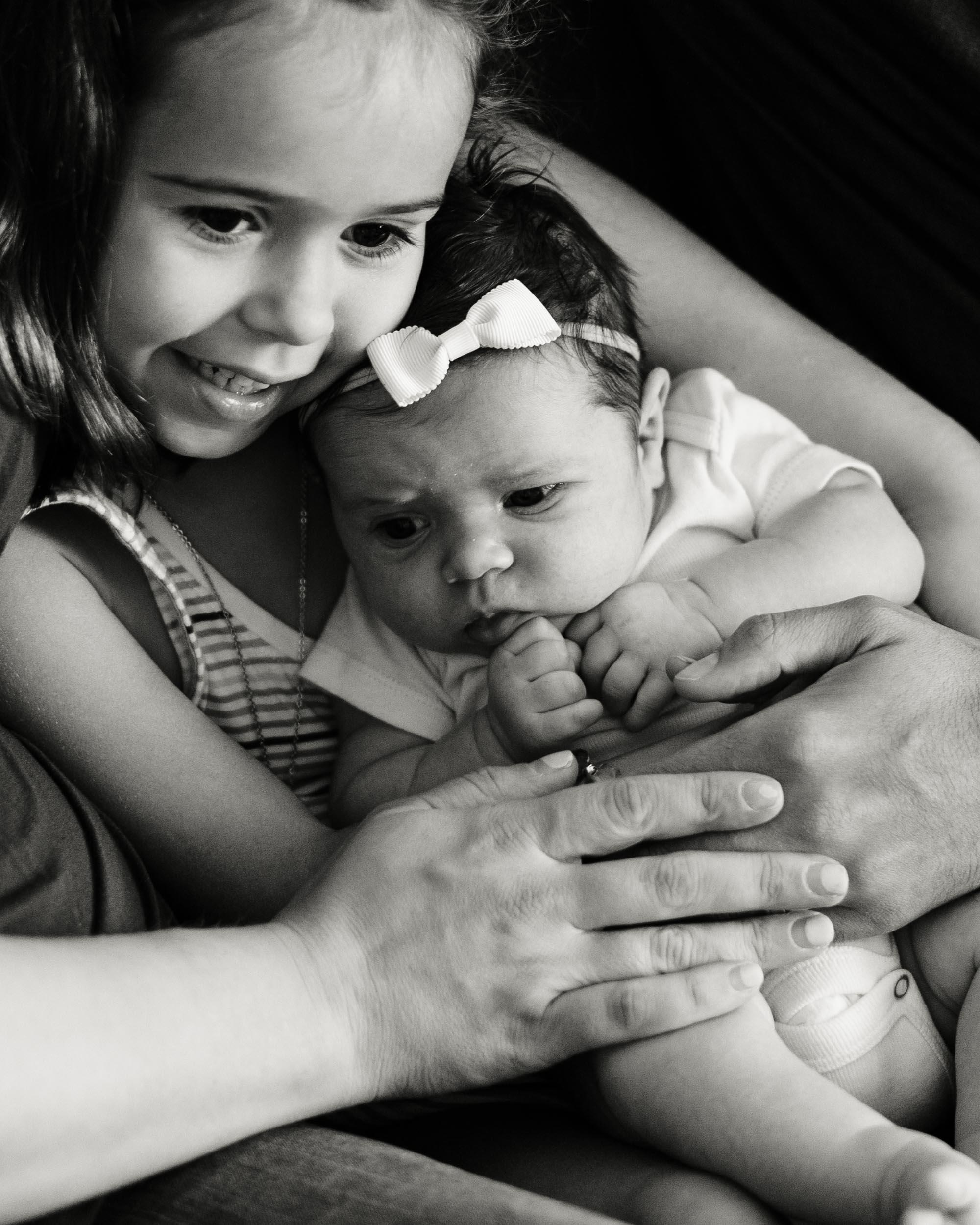 holding her newborn sister