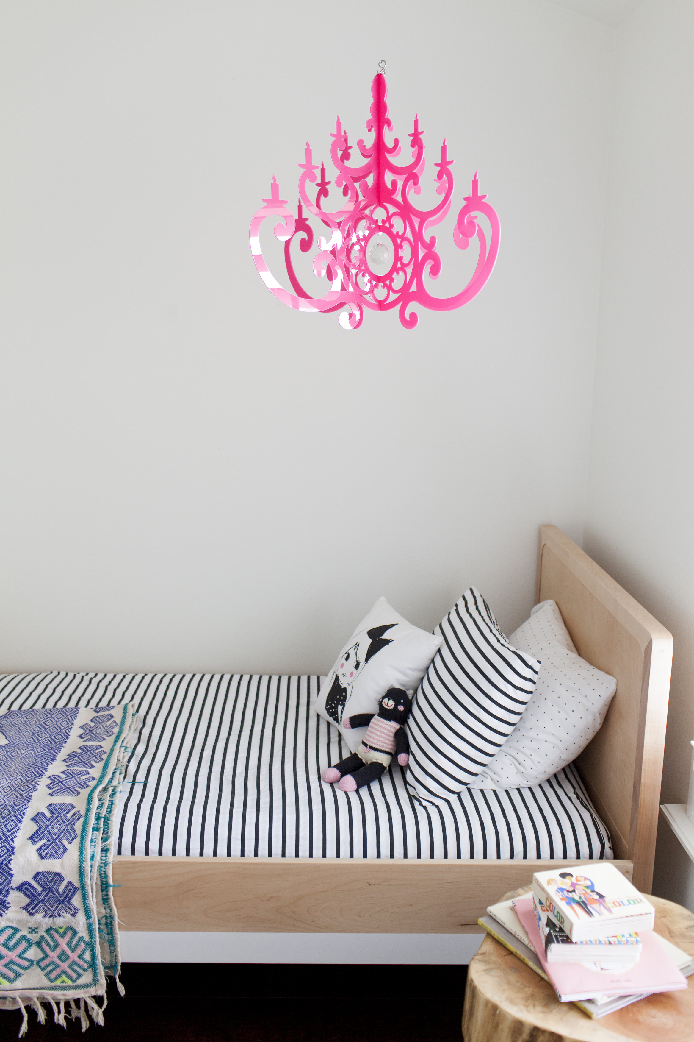 Shades of pink with our hot pink fancy chandelier, pink in bedspread, pink in books, pink in stuffed cat, pink on pillow. Perfect!
