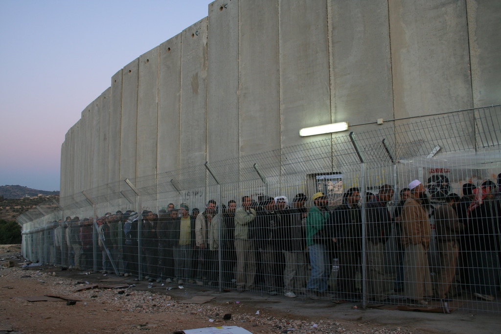 Men and women from all over the Southern West Bank stand in line for hours each morning on their way to work outside of Bethlehem.