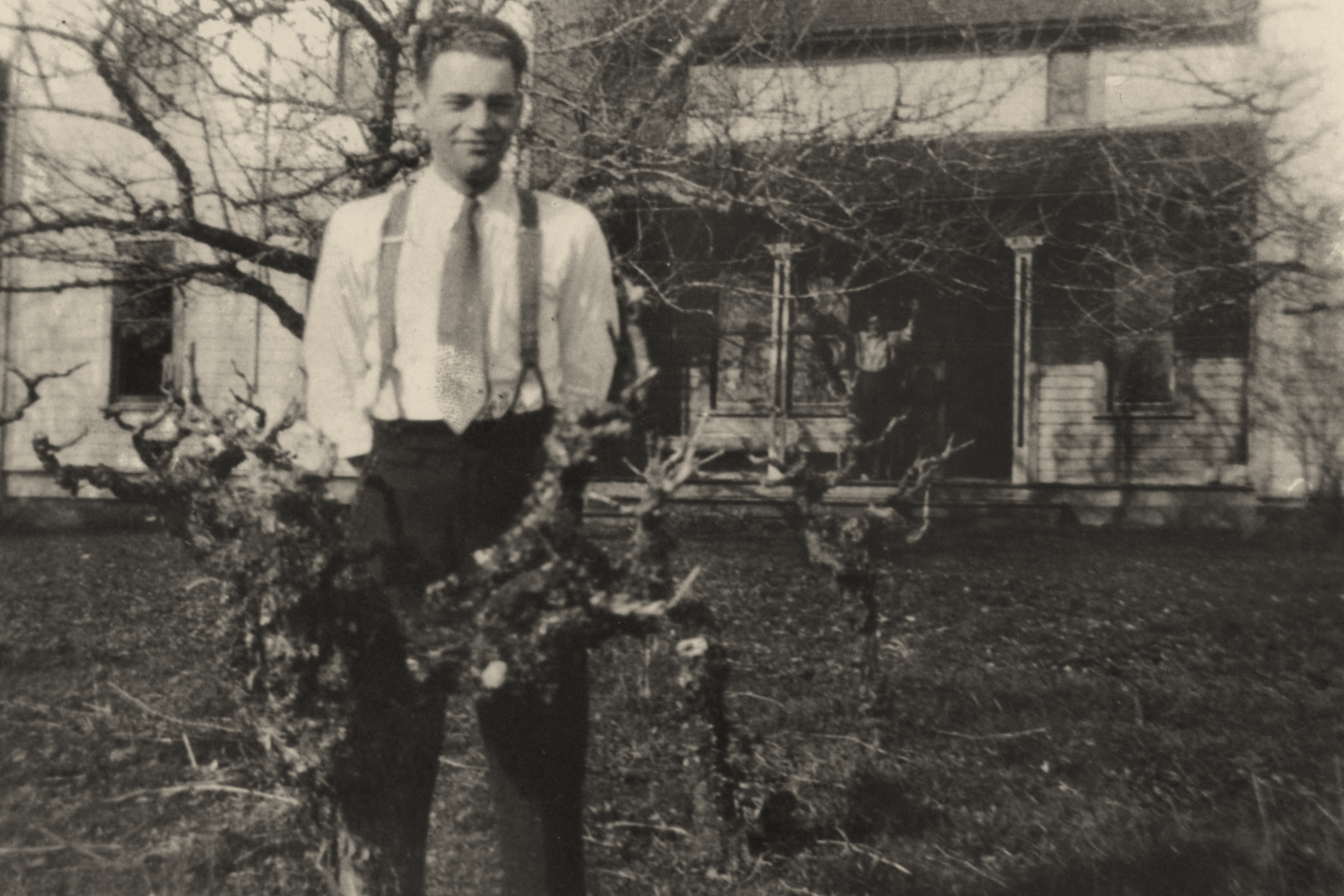 Date of image unknown, Ernest Rueter in front of vines, Adolf on porch.
