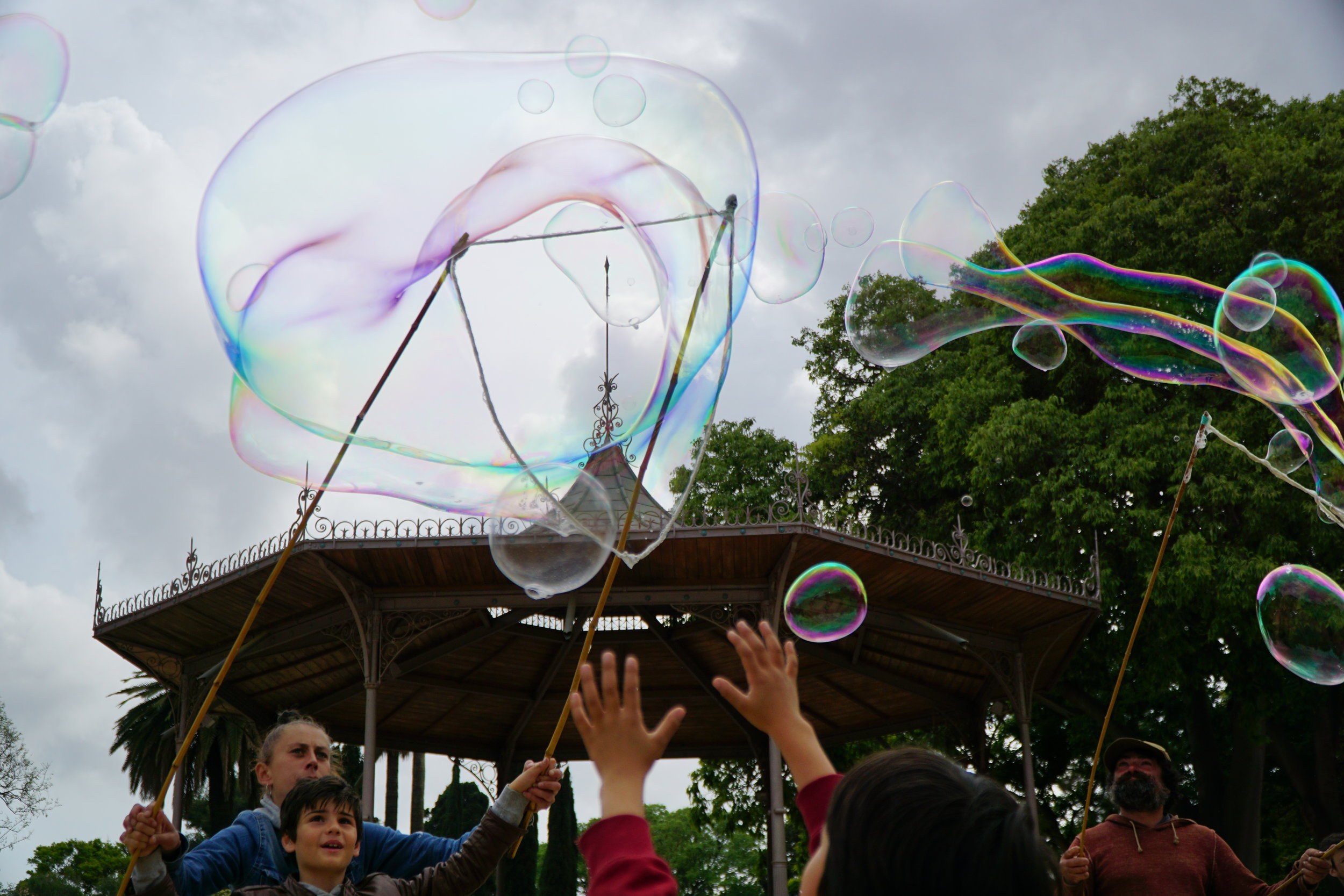 Catching Bubbles 4/30/2017 - I journeyed through a park today and noticed children catching bubbles. The street vendor used two pieces of wooden rods accompanied with rope to manifest these large bubbles.The local children in  joyful jamboree, jumped and jammed to one another's jovial praises. Also bringing me joy.It reminded me of a time when I was also their age and could let the fluid motions of colors in 3D form provide vast entertainment.I was reminded of how the simple things in life can bring happiness to many and how I neglected the blessings of my five senses.