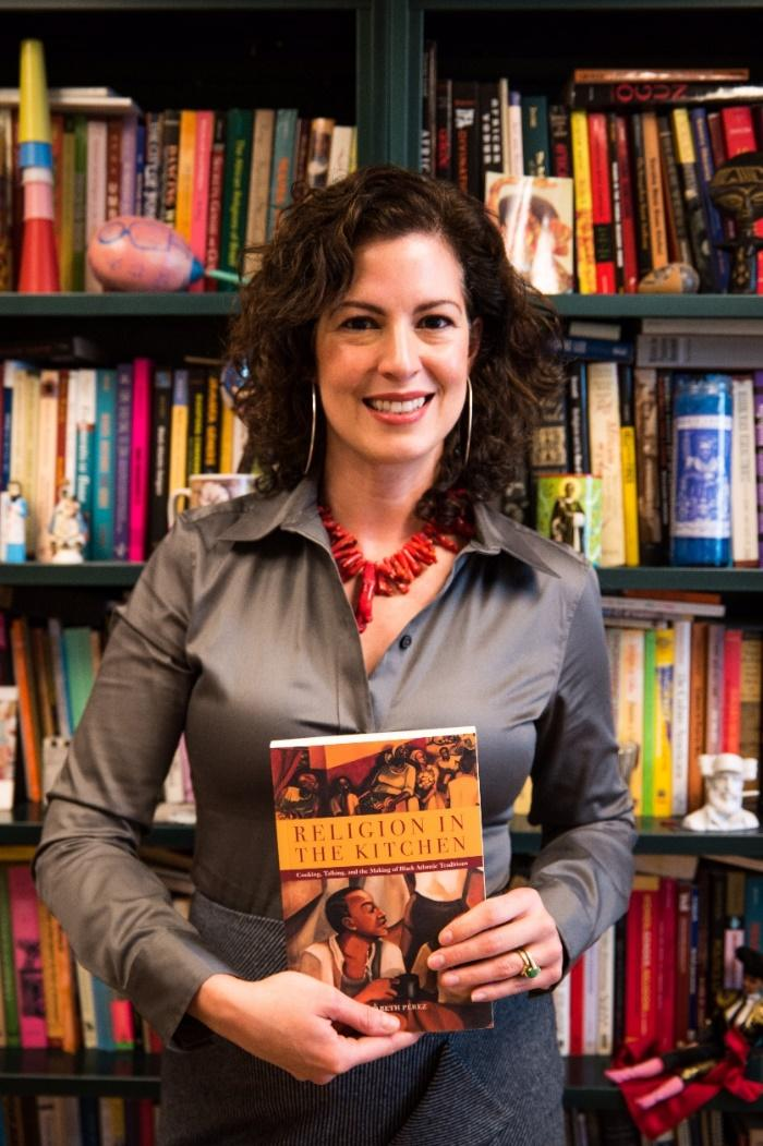 Elizabeth Pérez with her first book,  Religion in the Kitchen: Cooking,Talking, and the Making of Black Atlantic Traditions , in her office at UCSB.