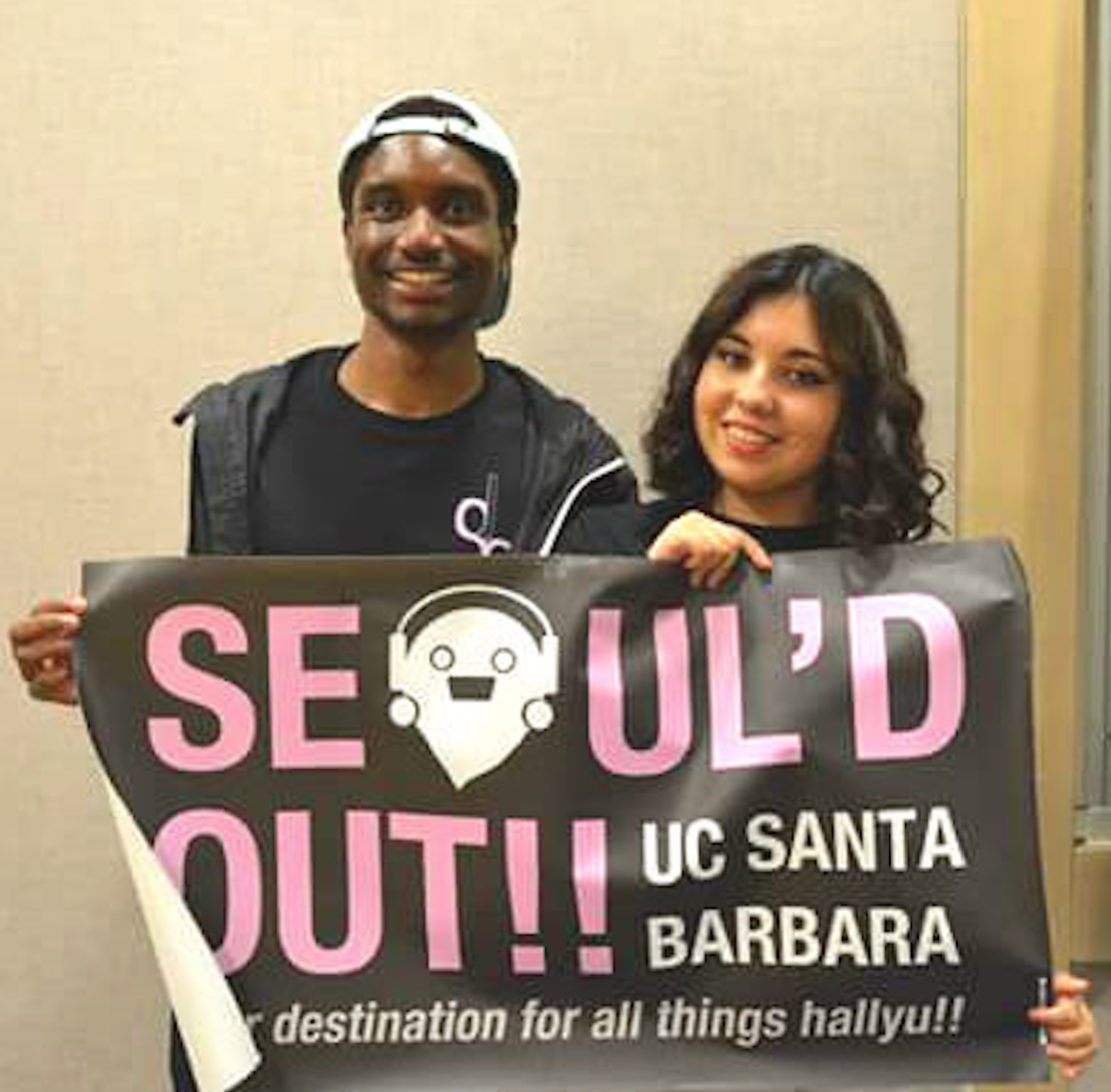 Co-Presidents of Seoul'd Out, Devin Clark and Samantha Mejia, pose together with the club's banner. (Photo courtesy of Seoul'd Out).