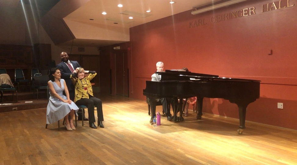 """Mezzo-soprano Frederica von Stade (in yellow), Kelly Guerra, and Byron Mayes acting out a hairdressing scene from the aria  The Barber of Seville  during a UCSB """"Guest Artist Masterclass."""""""