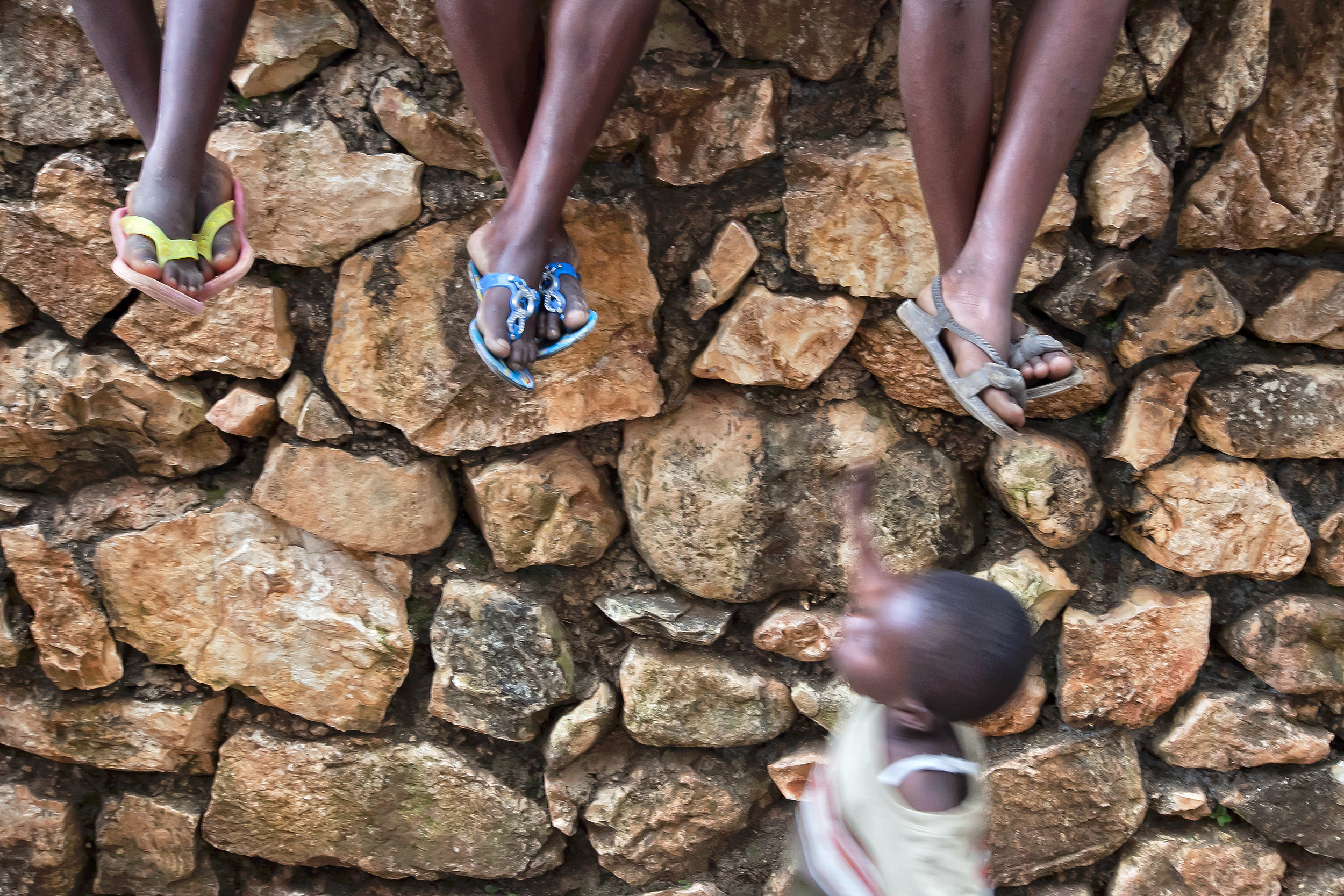 Shoes worn by Haitian children are often worn or broken.