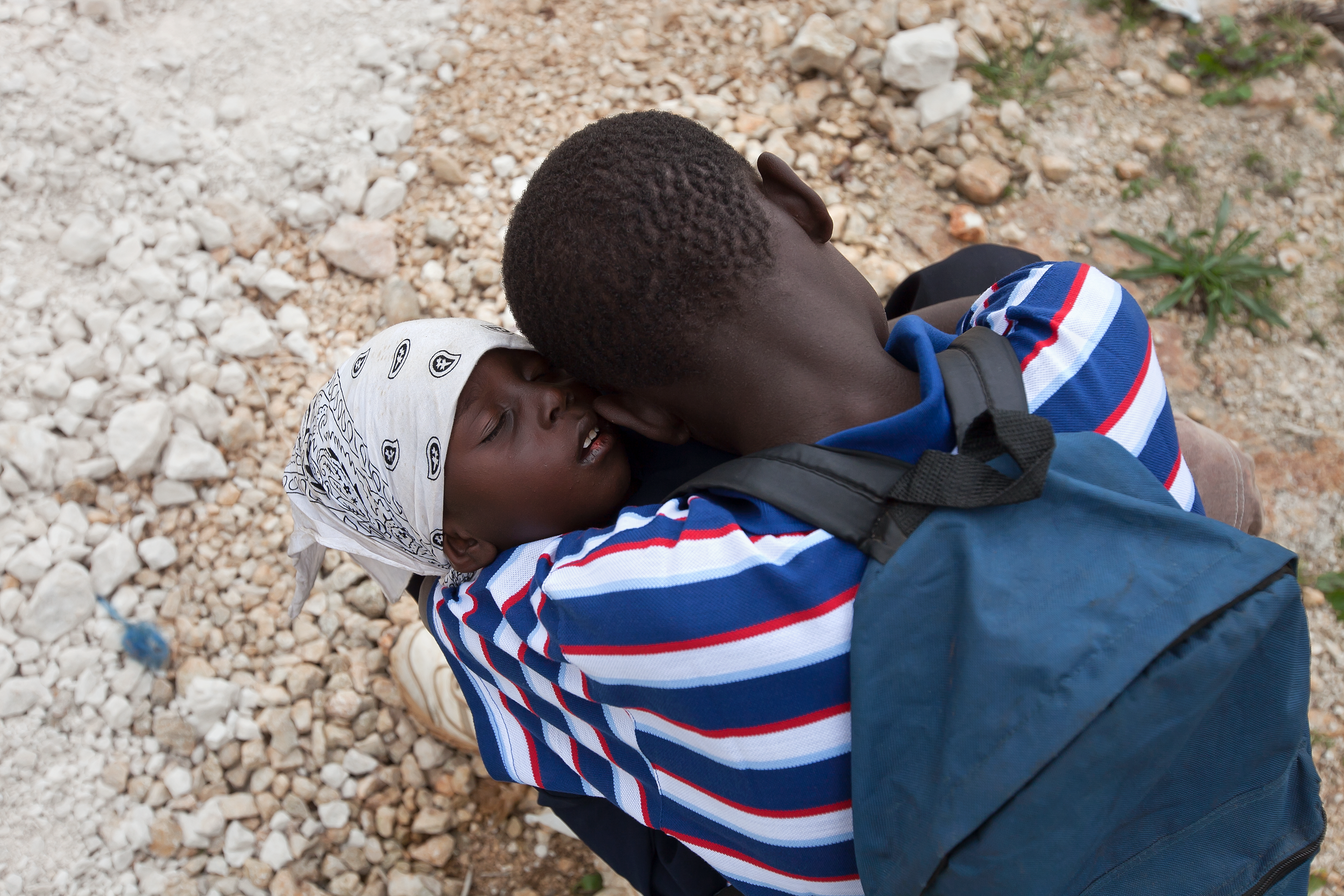 A Haitian man holds his sick child while waiting for care at the MTM clinic in Gramothe,Haiti.