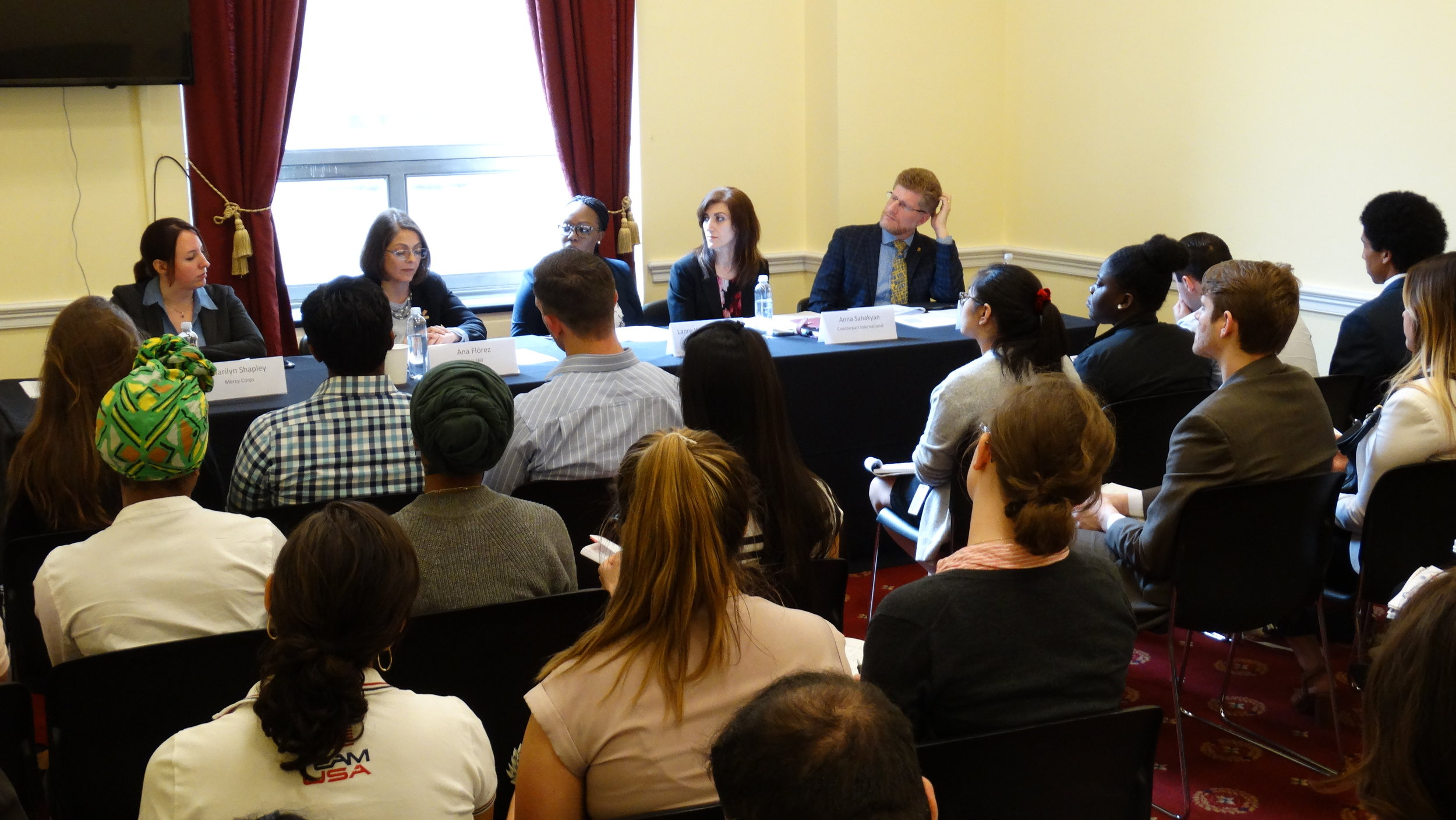 Above: Expert panel speaks to a packed room at briefing on aid in Northern Triangle