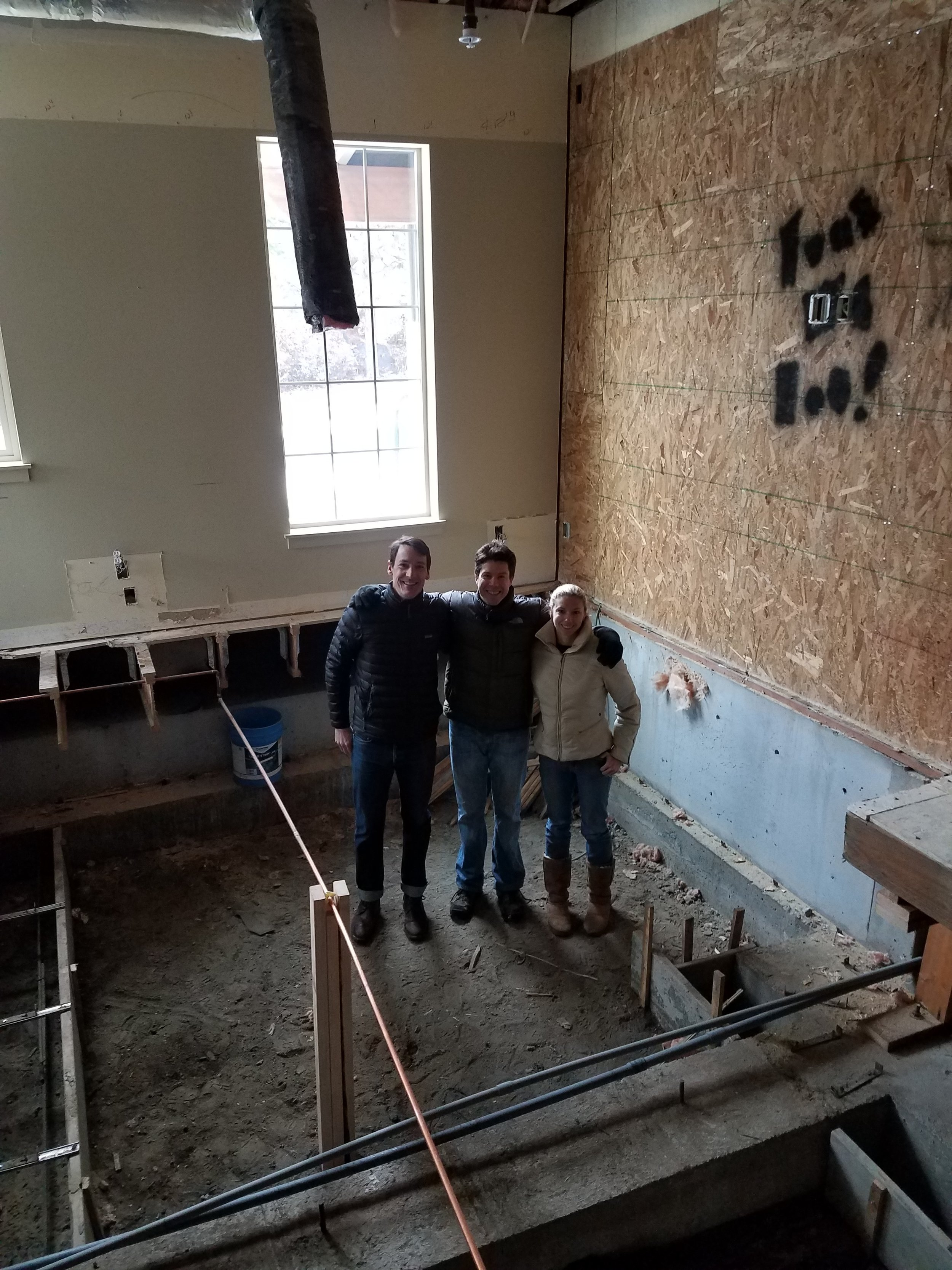 Dr's Dujowich, Vaughan, and Bentley standing in a pit where concrete will be poured to support the weight of the CT.