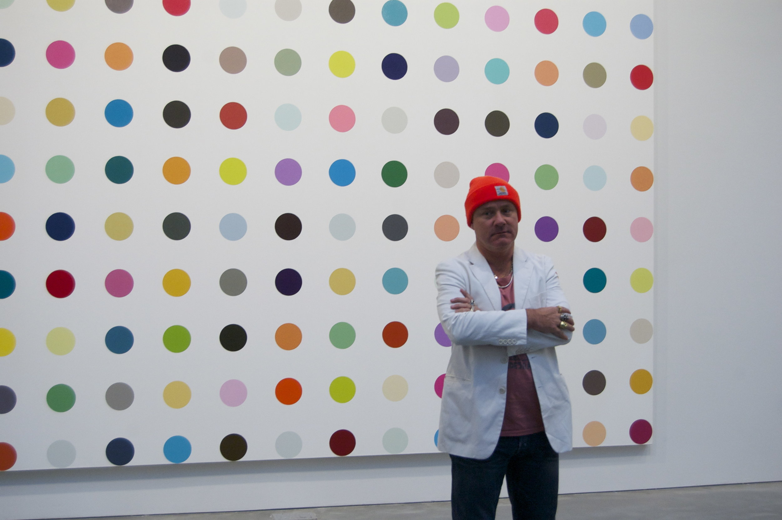 Artist Damian Hirst posing in front of  Oleoylsarcosine , the world's most valuable joke. (Photo by Andrew Russeth.)