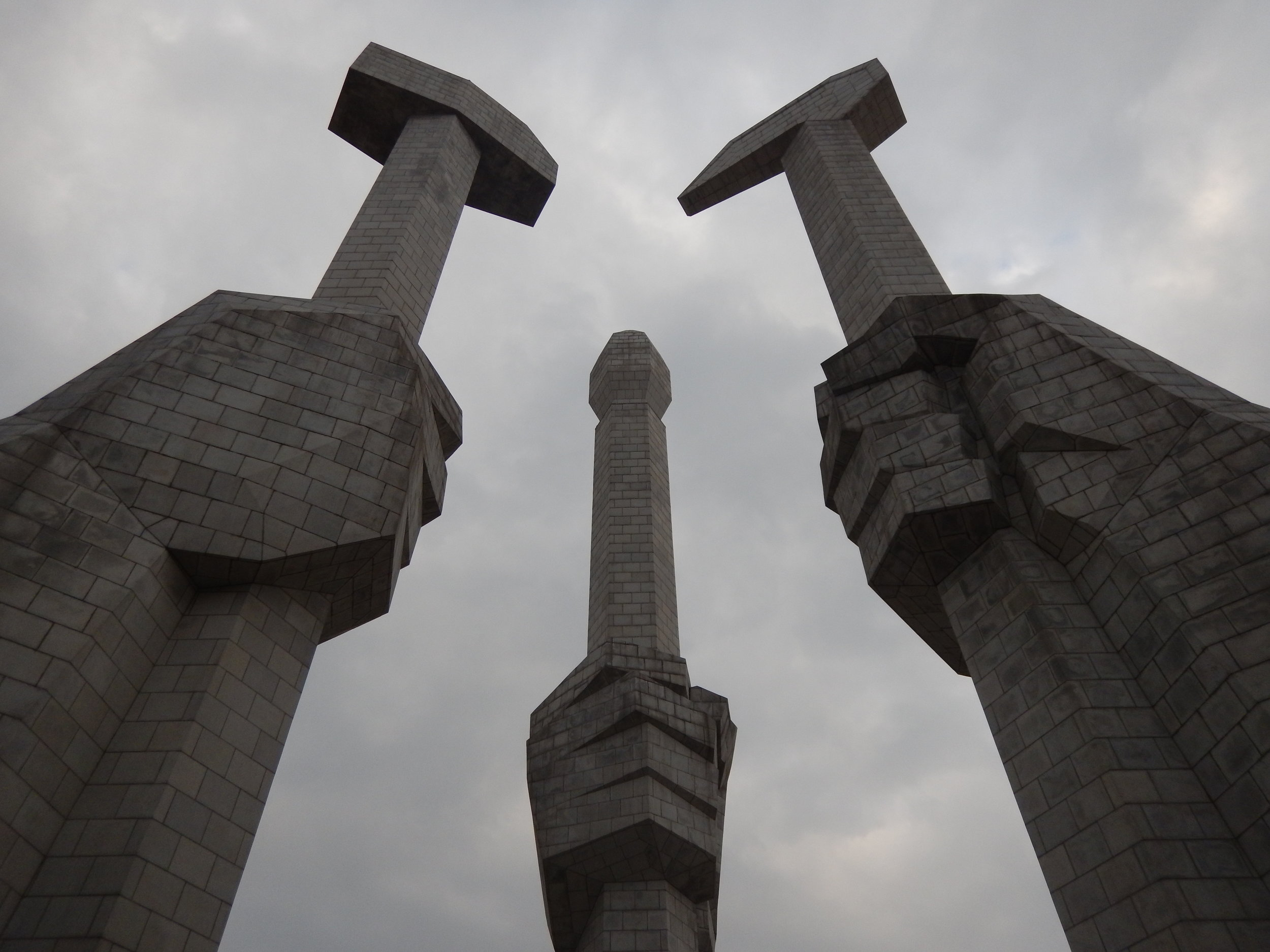 The Monument to the Foundation of the Party features three hands holding a hammer, representing the worker, a sickle, representing the farmer, and a paintbrush, representing the intellectual – these three tools are the official symbols of the ruling Worker's Party of Korea. (Photo by Ethan Jakob Craft.)