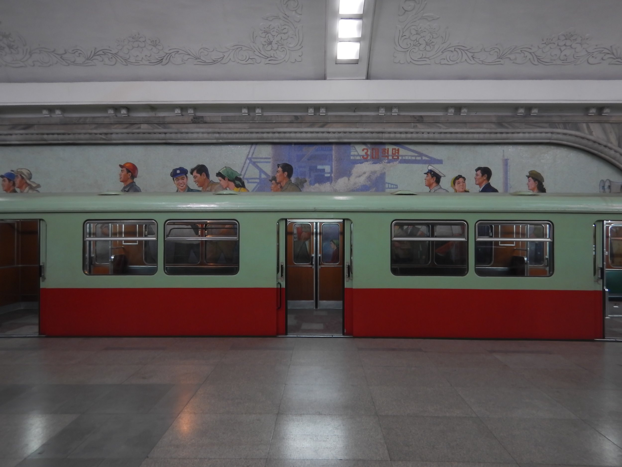 An empty subway car parked in thr Pyongyang Metro's Puhung Station, found in the southern part of the city. Visible behind the car is a tile mosaic depicting the life of average North Korean workers. (Photo by Ethan Jakob Craft.)