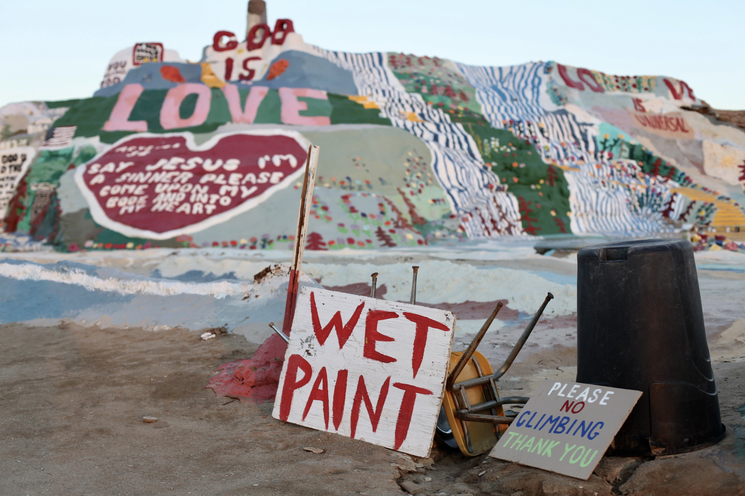 A sign warns tourists about a freshly painted section of Salvation Mountain in Slab City, Calif. on Jan. 6, 2017.(Photo by Ethan Jakob Craft.)