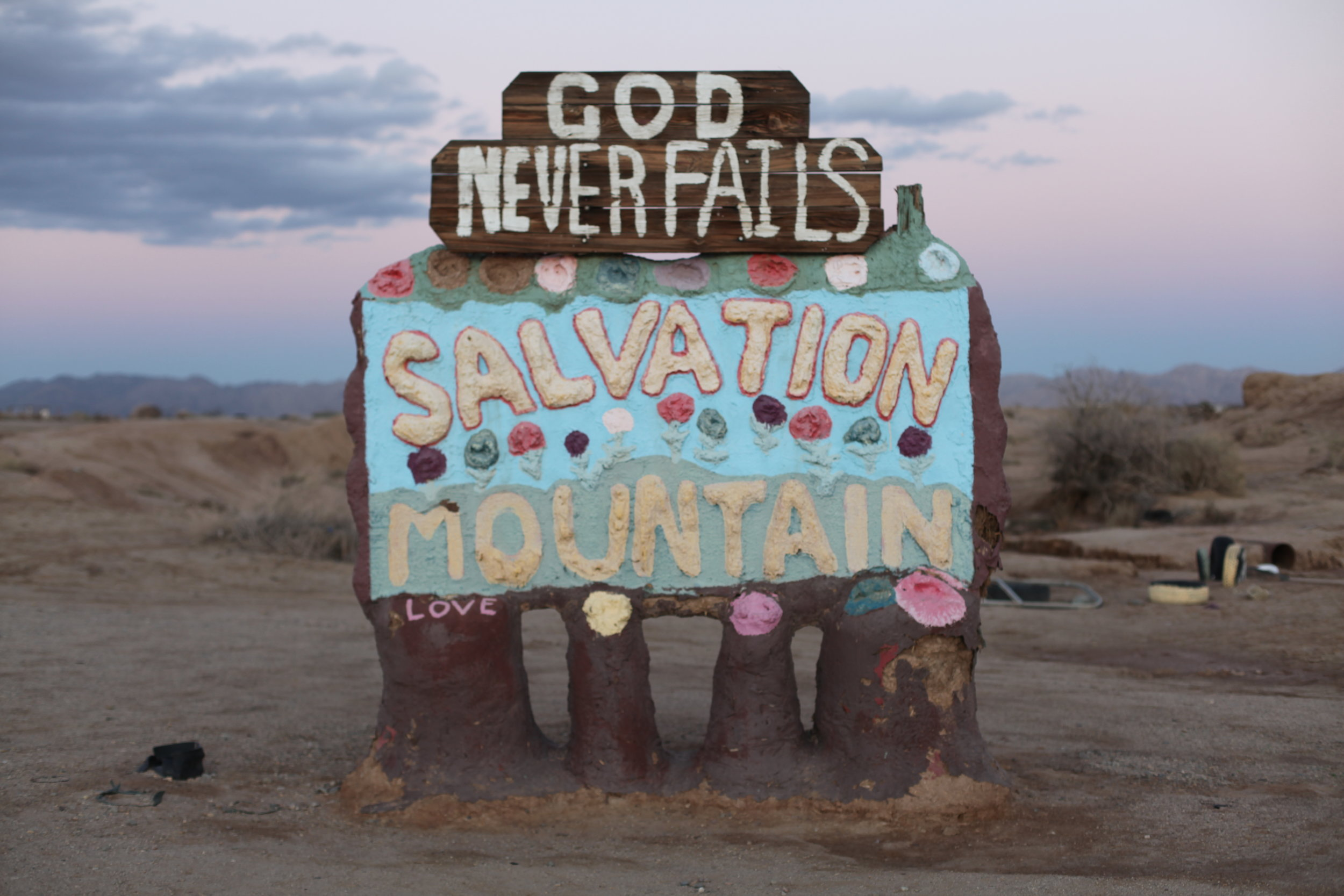 A crude sign welcomes visitors to Salvation Mountain in Slab City, Calif. at sunset on Jan. 6, 2017.(Photo by Ethan Jakob Craft.)