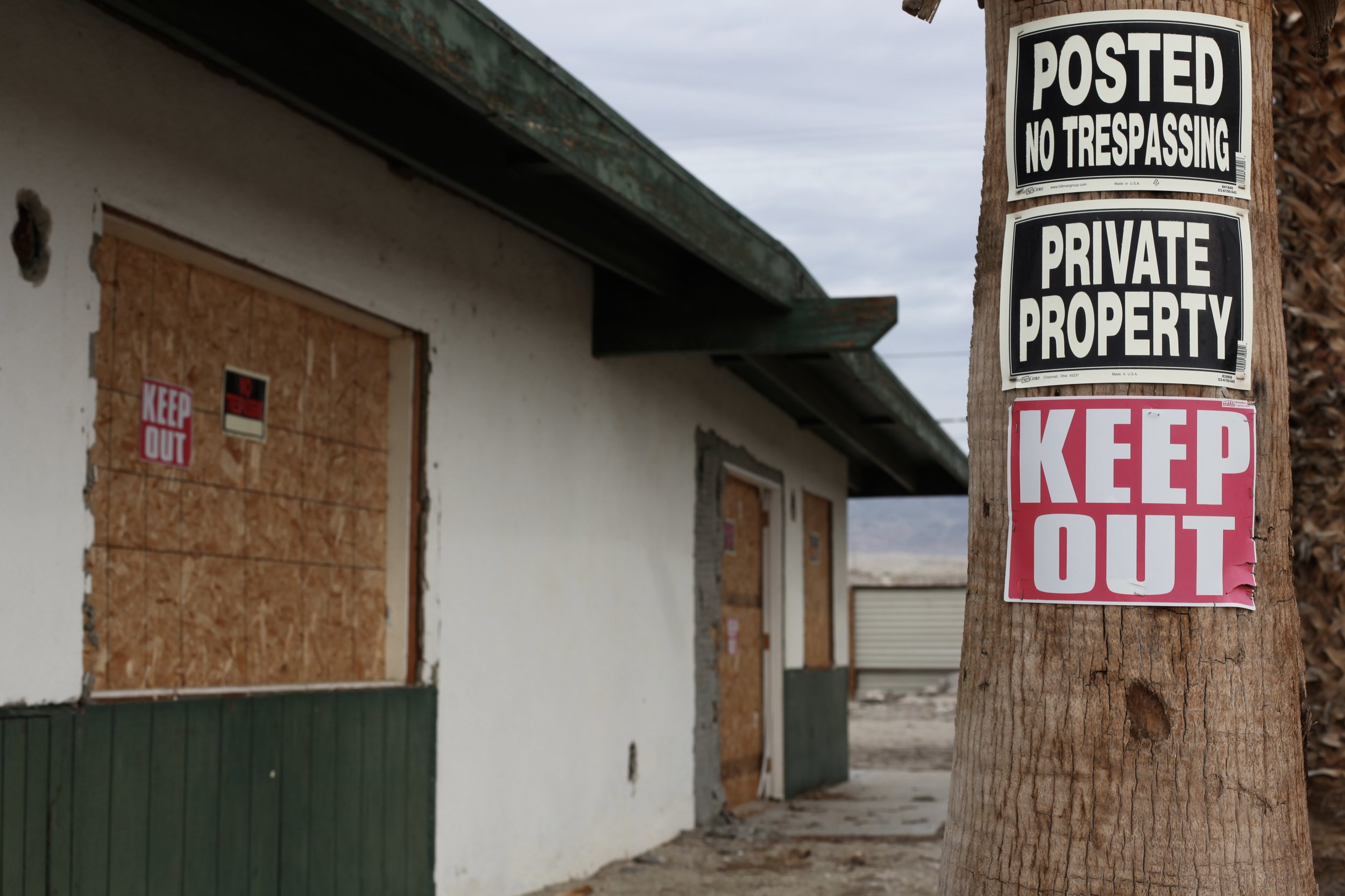 Multiple signs warn trespassers to stay away from an abandoned housing complex in North Shore, Calif. on Jan. 7, 2017.(Photo by Ethan Jakob Craft.)