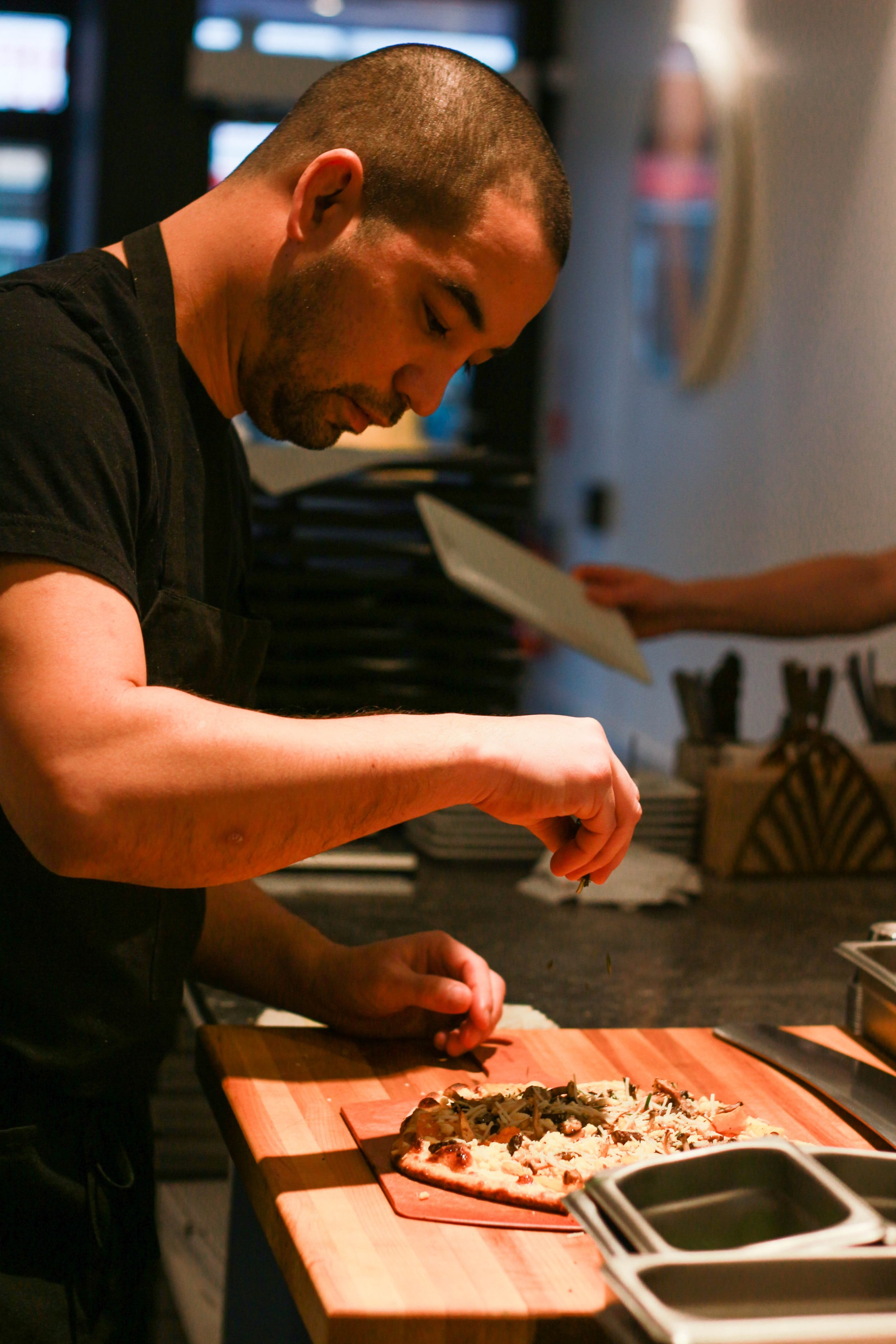 Head chef Aaron Okada deftly garnishes the Toronto-exclusive pizza, The Harvest, with a sprinkle of plant-based parmesan cheese on a slow Saturday afternoon at Virtuous Pie. (The Unaffiliated Press/Kayla Zhu)
