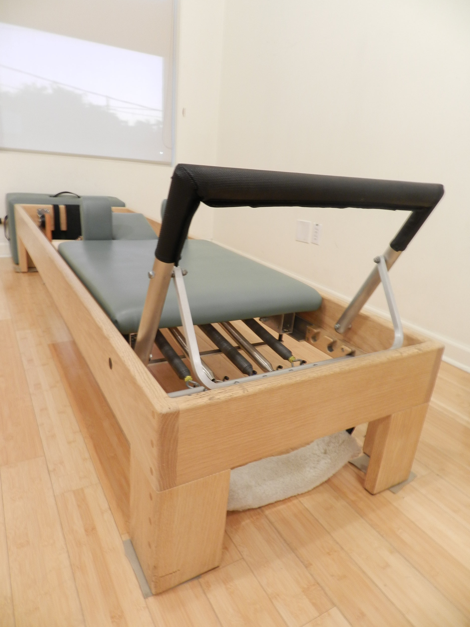 Invest in a few private sessions on the Pilates apparatus (reformer pictured above). You will enjoy one on one attention and become accustomed to the springs and moving parts and pieces you'll need to manage in a group setting.