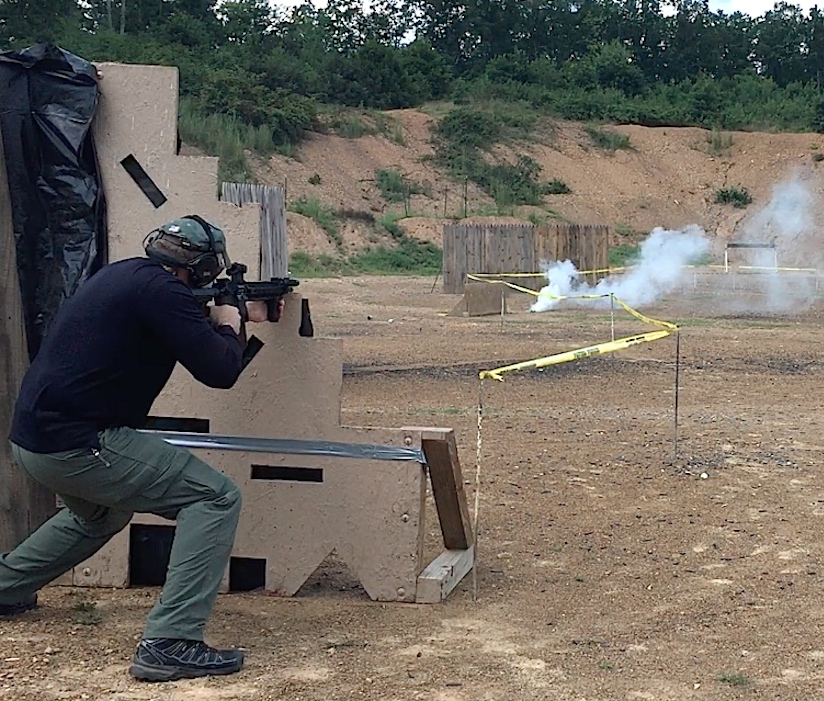 """Shooter engages steel plates from VTAC barricade, as non-pyrotechnic Sport Smoke grenade begins to obscure the """"street"""" in the urban stage."""