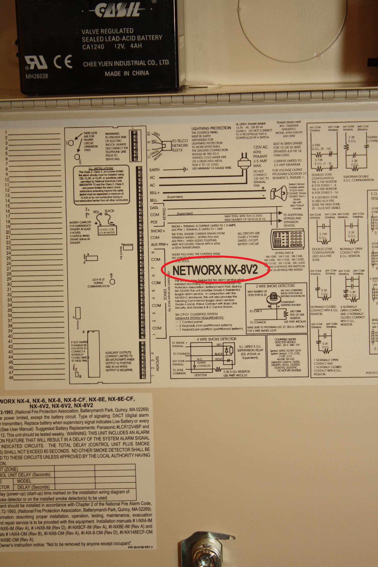 Hookup panel diagram for the Caddex NX 1448e Fixed English alarm system showing the location of the serial number - NCA Alarms Nashville TN