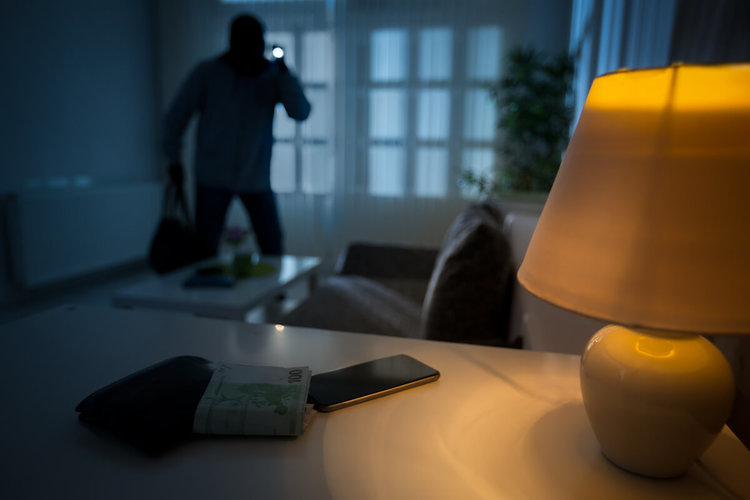Photo of burgler entering living room at night, phone in foreground